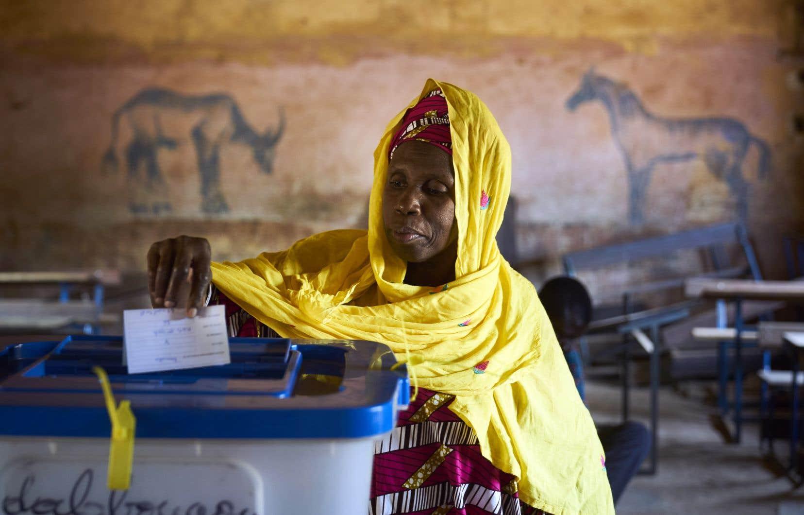 Une femme enregistre son vote au second tour des élections à Bamako, dimanche.