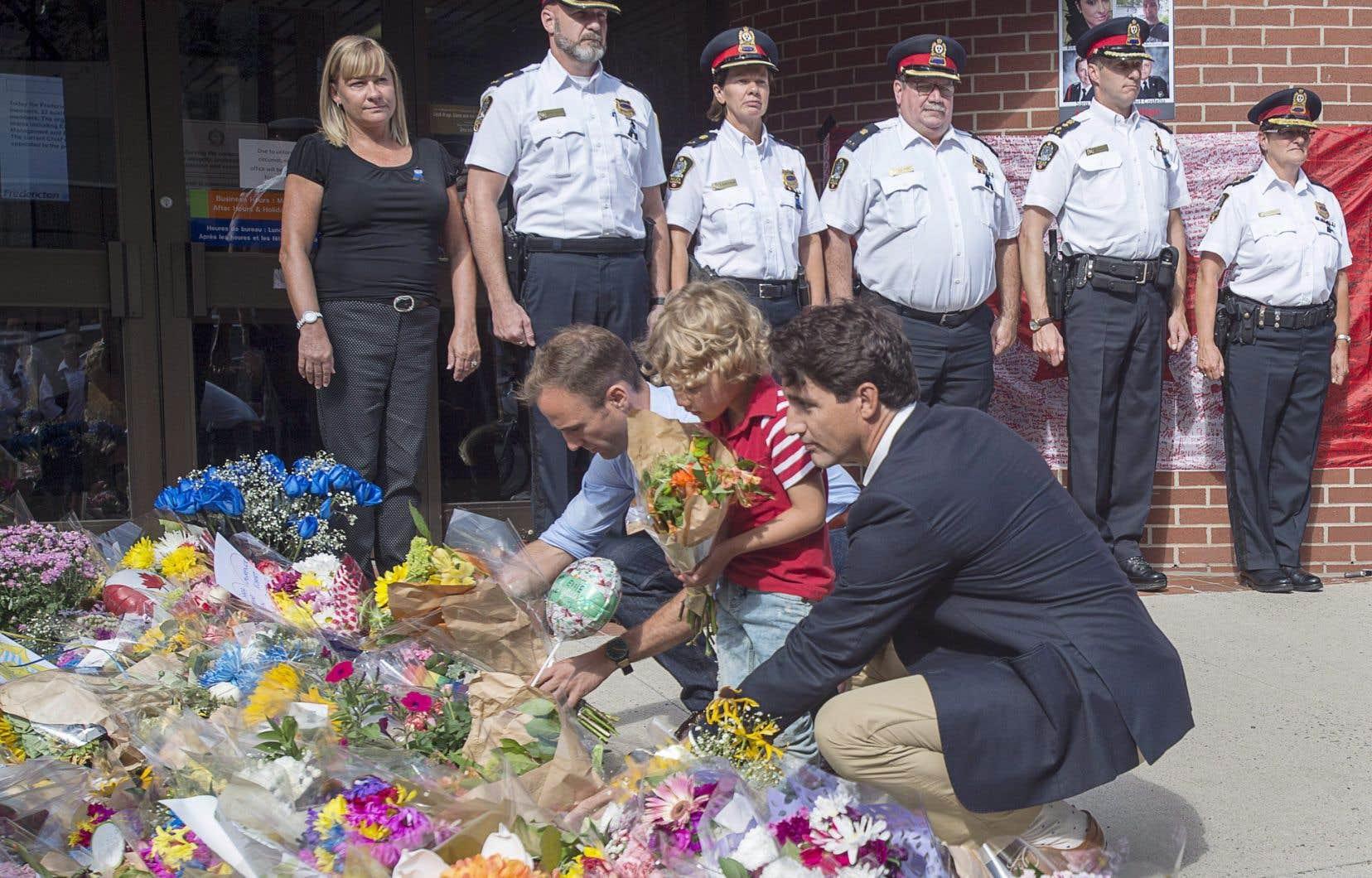Accompagné de son fils Hadrien, le premier ministre Justin Trudeau s'est rendu au quartier général de la Force policière de Fredericton pour déposer des fleurs au mémorial dédié aux victimes.