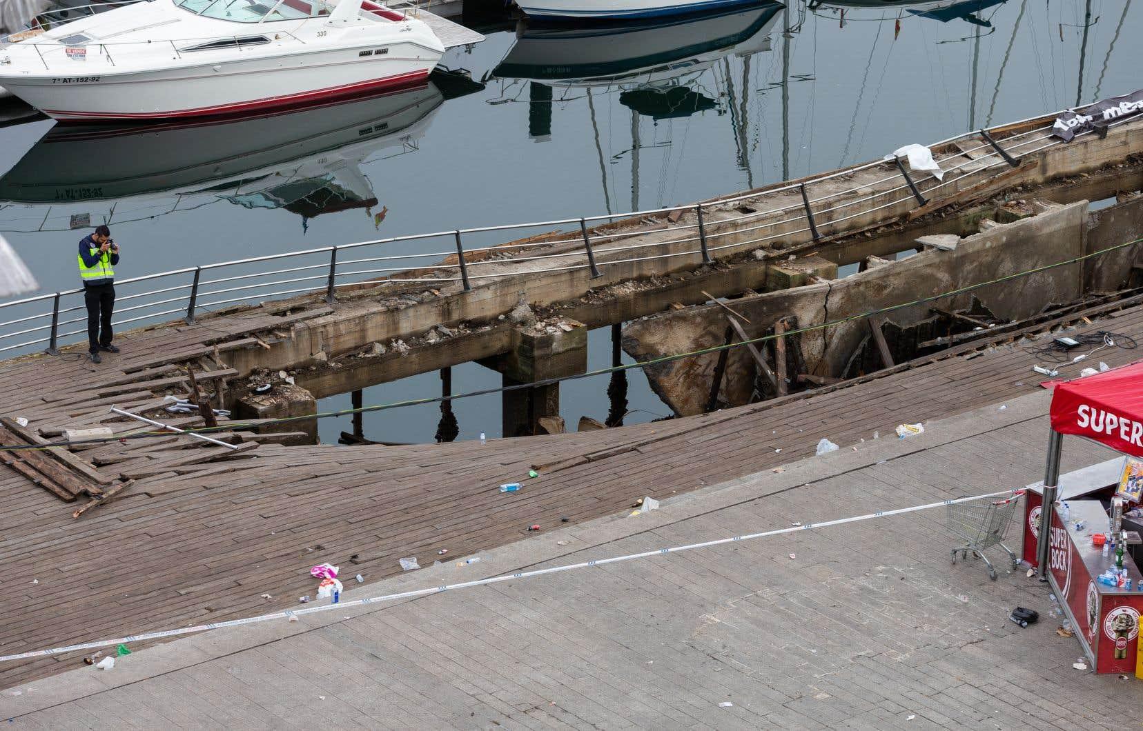 Un policier inspecte le quai de Vigo après qu'une section de la promenade en bois se soit soudainement effondrée avec des gens qui regardaient un artiste rap peu avant minuit dimanche.