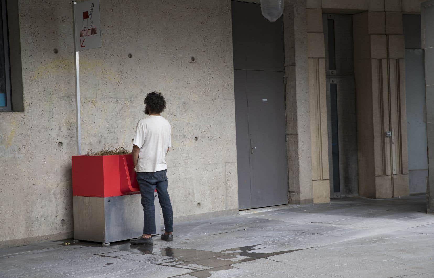 Un homme utilise un urinoir public «uritrottoir», près de la gare de Lyon à Paris.
