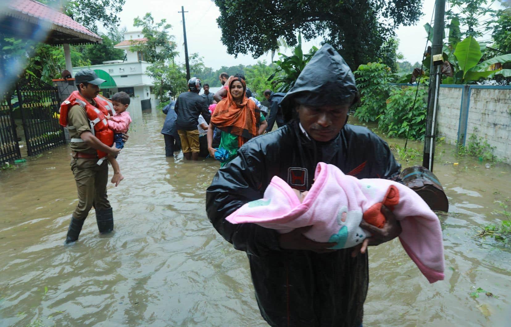 Des pompiers et secouristes évacuent les résidents d'une une zone inondée à Muppathadam, dans l'état indien du Kerala, le 15 août 2018.