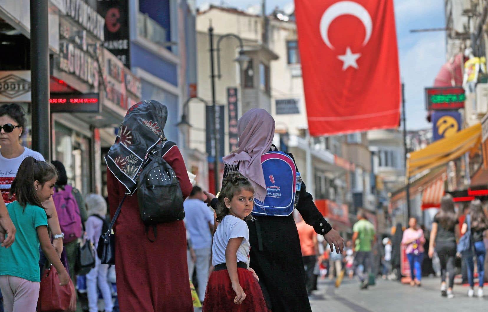 Des passants dans un marché d'Istanbul. Les tensions américano-turques ont précipité l'effondrement de la livre, qui a perdu plus de 40% de sa valeur face au billet vert et à l'euro depuis le début de l'année.