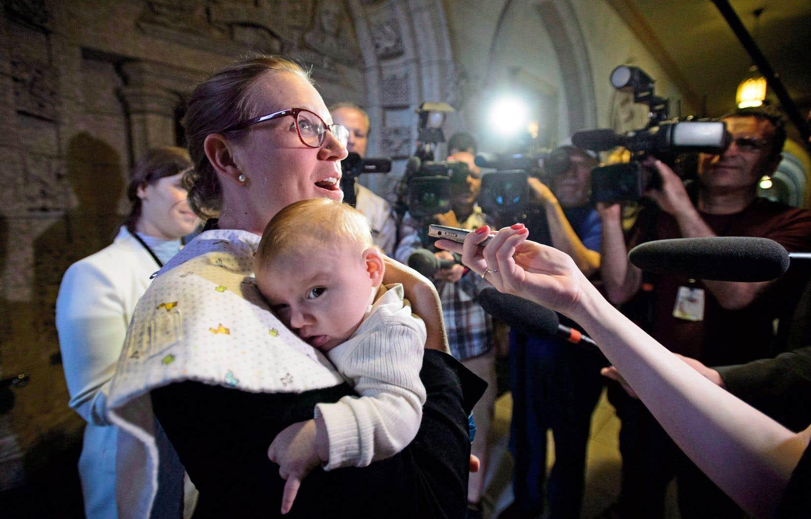 La ministre fédérale Karina Gould photographiée lors d'un point de presse avec son bébé dans les bras
