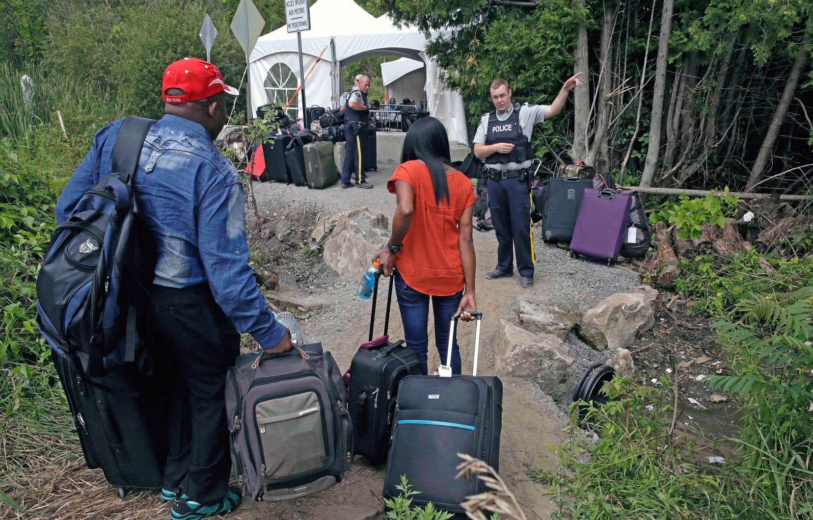 Un policier accueille des demandeurs d'asile qui ont franchi la frontière de manière irrégulière en empruntant le chemin Roxham.