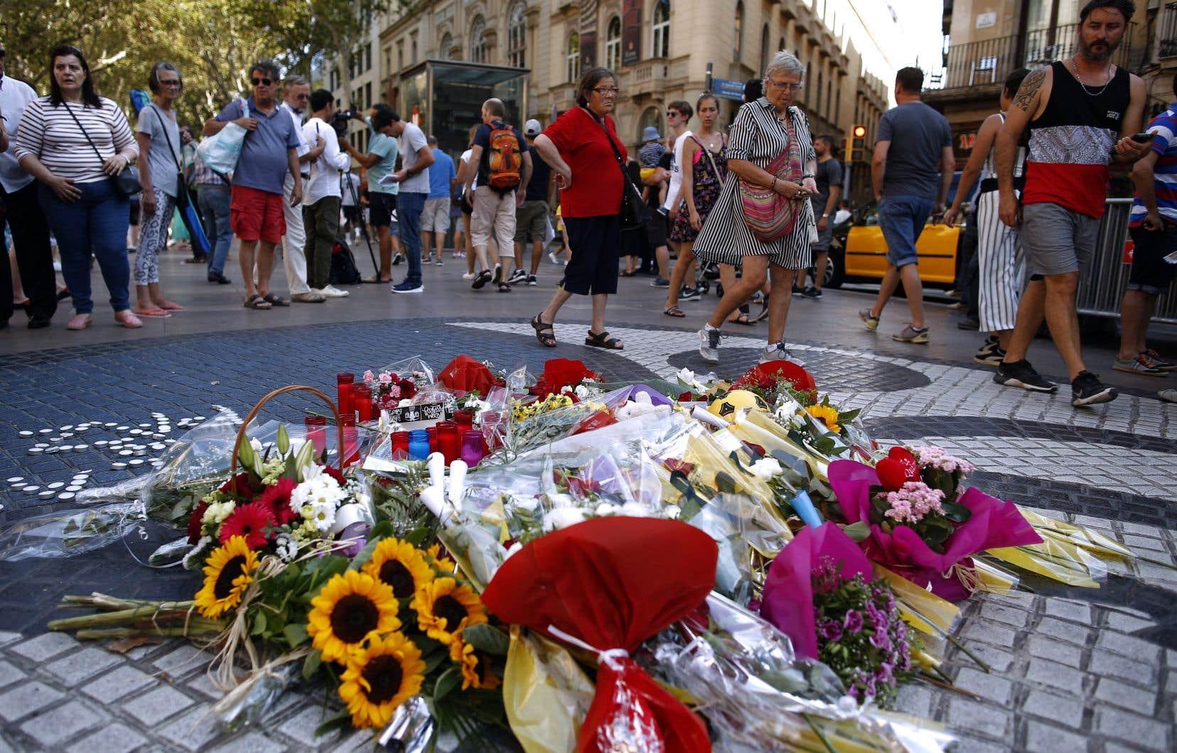 Des passants se recueillent sur les Ramblas à proximité d'un amas de fleurs, bougies et messages commémorant les attentats de Barcelone, le 17 août 2017.