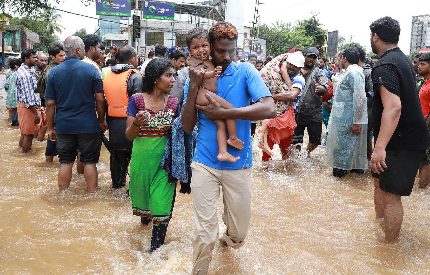 Des secouristes évacuent des résidents d'un quartier d'Aluva, dans l'état indien du Kerala, vendredi.