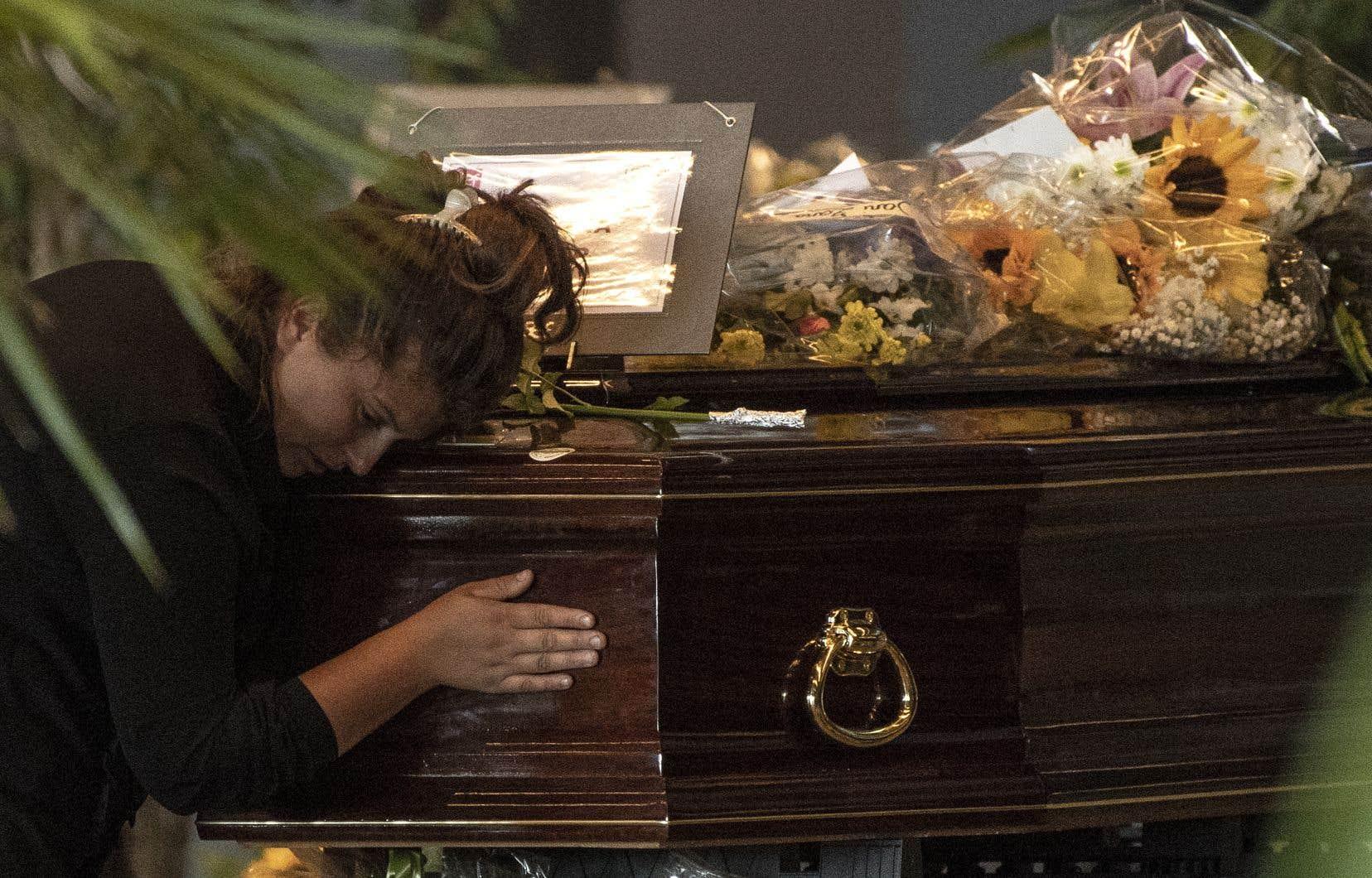 Une femme se recueille devant le cercueil d'une victime du viaduc de Gênes, vendredi.