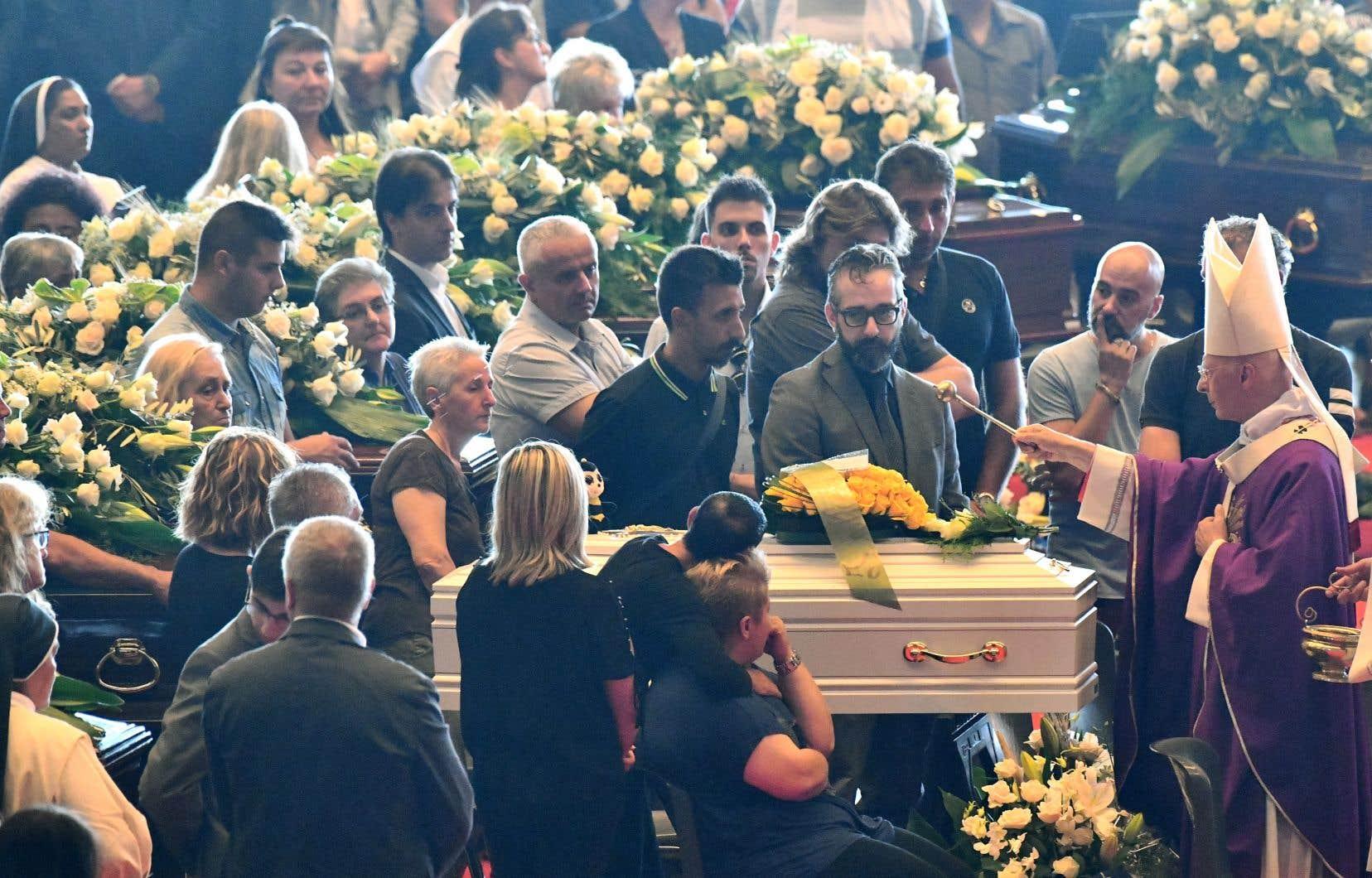 L'archevêque de Gênes, le cardinal Angelo Bagnasco, bénit les cercueils lors des funérailles nationales des victimes de l'effondrement du pont de Morandi, à Gênes, le 18 août 2018.