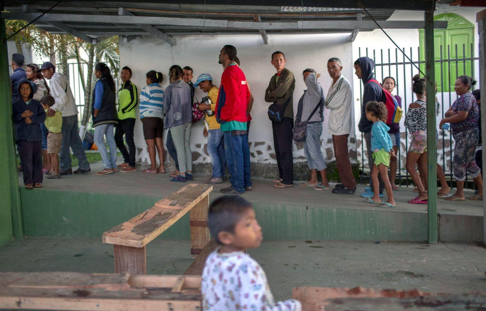 Des Vénézuéliens s'apprêtent à recevoir à déjeuner dans la paroisse du prêtre espagnol Jose Lopez Fernandez de Bobadilla, à Pacaraima.