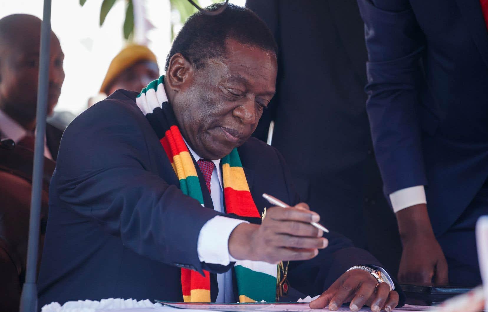 Le président zimbabwéen, Emmerson Mnangagwa, signe des documents après avoir prêté serment à Harare, le 26 août 2018.