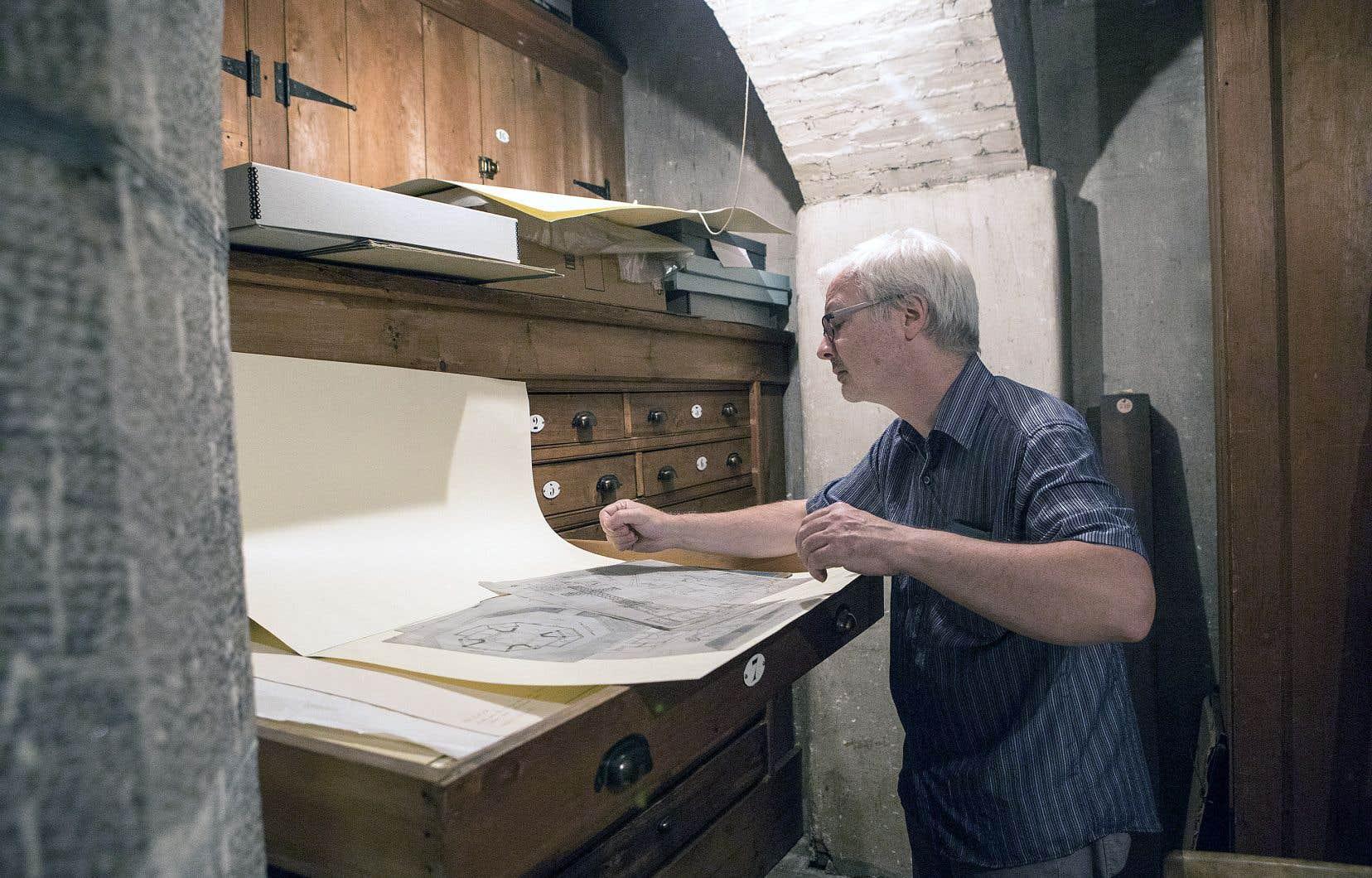 Marc Lacasse, coordinateur au service des archives de l'Univers culturel de Saint-Sulpice, examine des plans de la ville de Montréal.