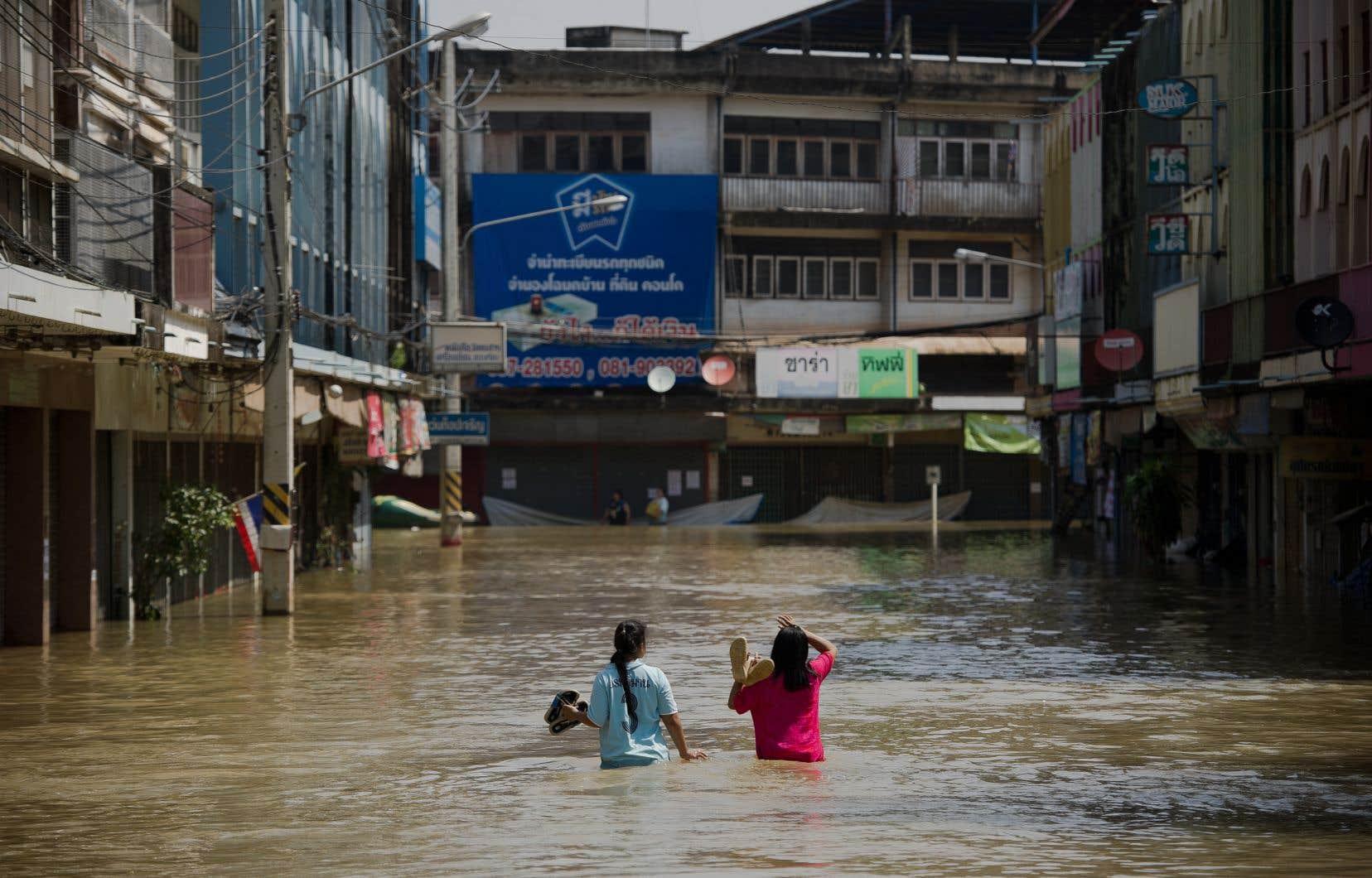 Les inondations sont fréquentes dans la région de Bangkok. Sur cette photo d'octobre 2013, deux jeunes femmes traversent la rue inondée à Kabin Bur, dans l'est de la grande ville.