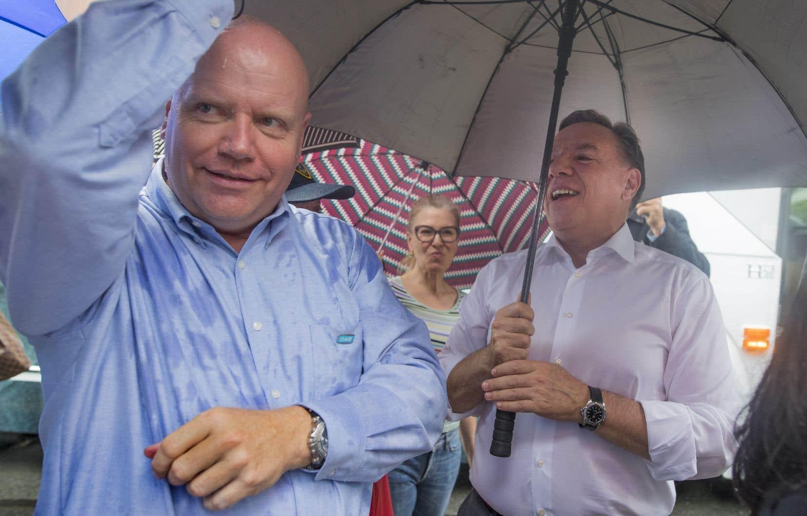 Le candidat caquiste Ian Lafrenière et le chef, François Legault, par un temps pluvieux, samedi