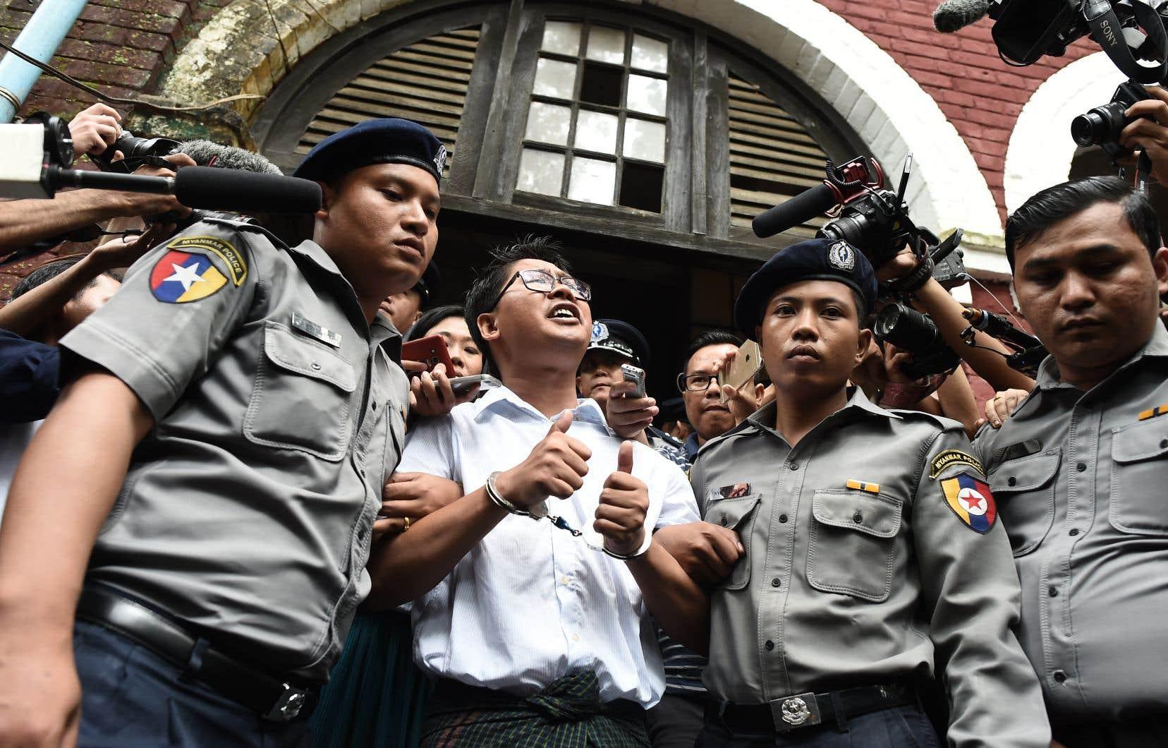 Wa Lone (au centre), l'un des journalistes écroués, est escorté par la police après avoir entendu sa sentence.