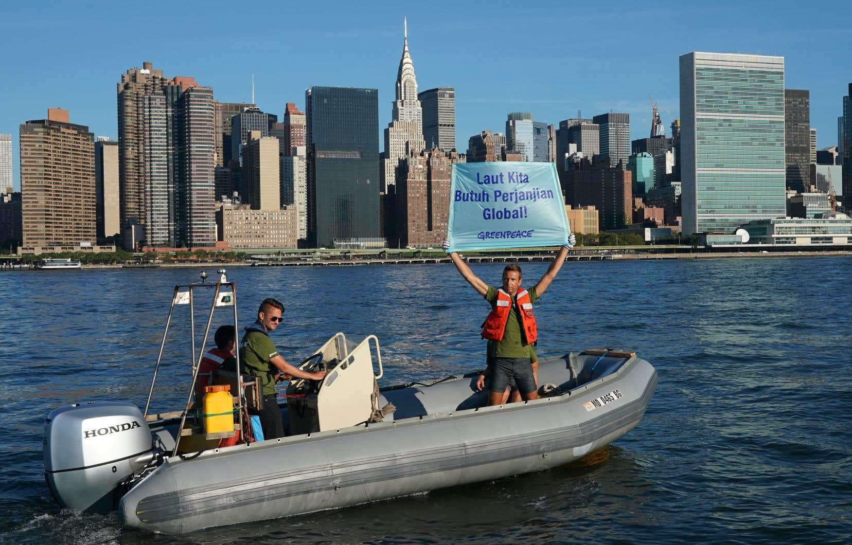 Des militants de Greenpeace tiennent une bannière près des Nations unies pour attirer l'attention sur le traité qui doit permettre de mieux préserver des océans et des fonds marins.