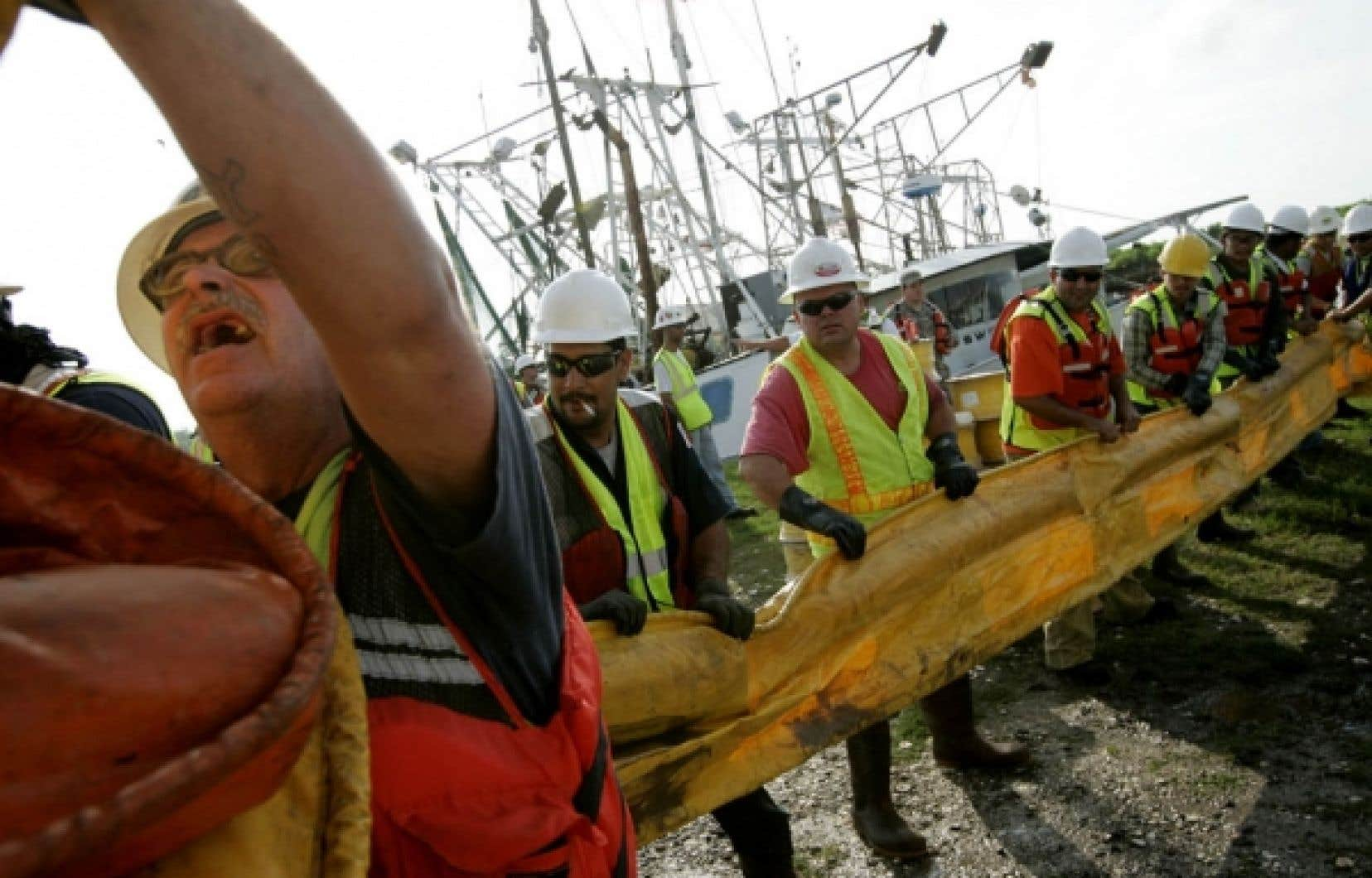 En Louisiane, des travailleurs se mettaient à plusieurs pour décharger des estacades flottantes servant à contenir le pétrole dans certaines zones.