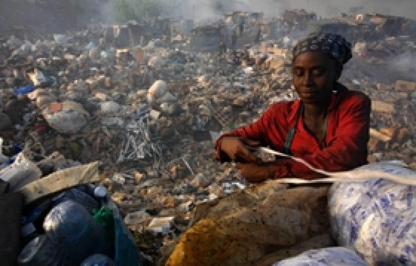 Une femme attache un sac de déchets qu'elle a récupérés dans le dépotoir d'Olusosun, au Nigeria. On gaspille beaucoup moins dans les pays pauvres et on récupère tout ce qu'on peut de façon artisanale.