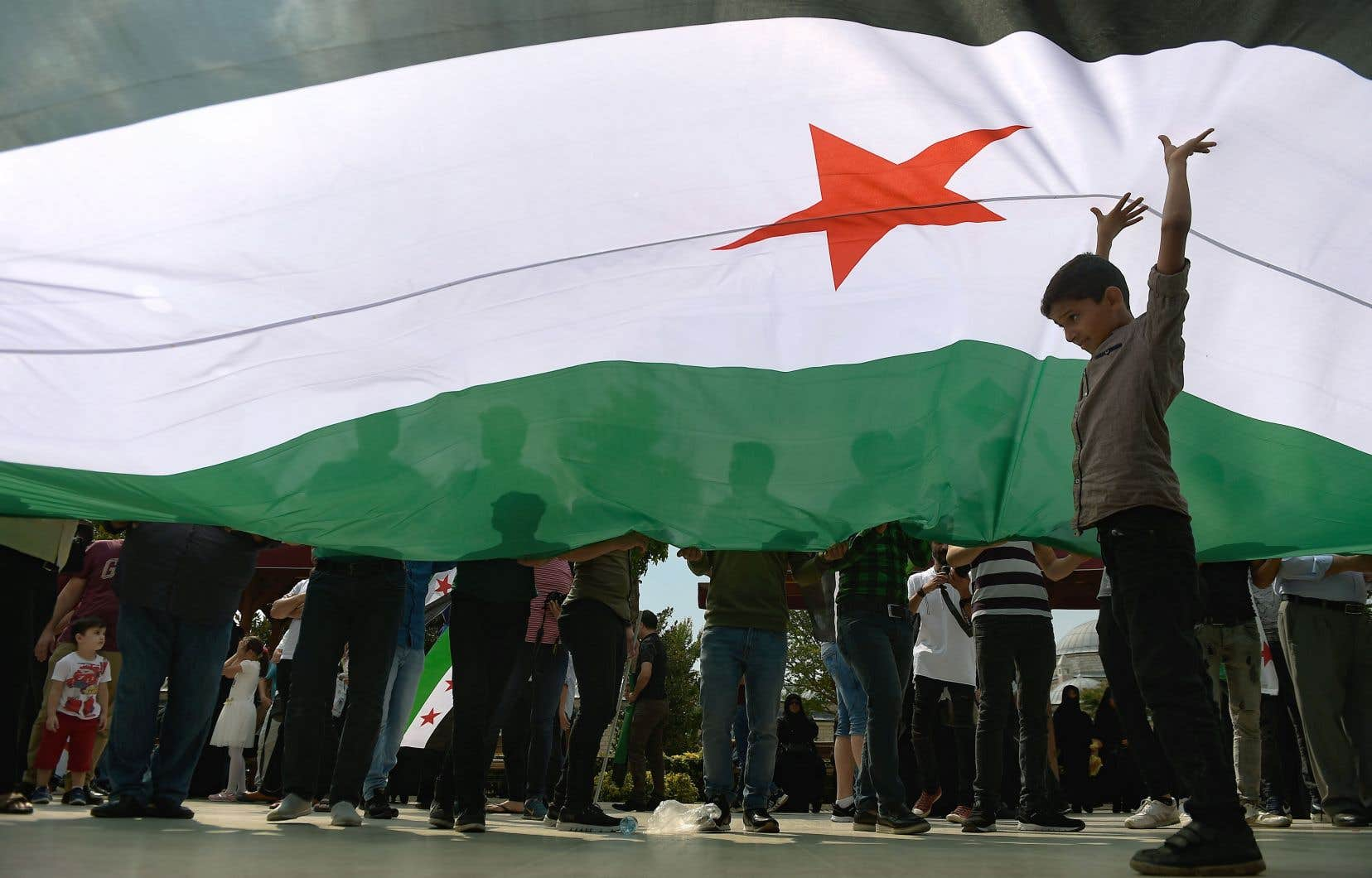Un enfant s'est placé sous un drapeau de l'Armée syrienne libre, au cours d'une manifestation vendredi à Istanbul en Turquie contre une opération militaire syrienne dans la région d'Idleb.