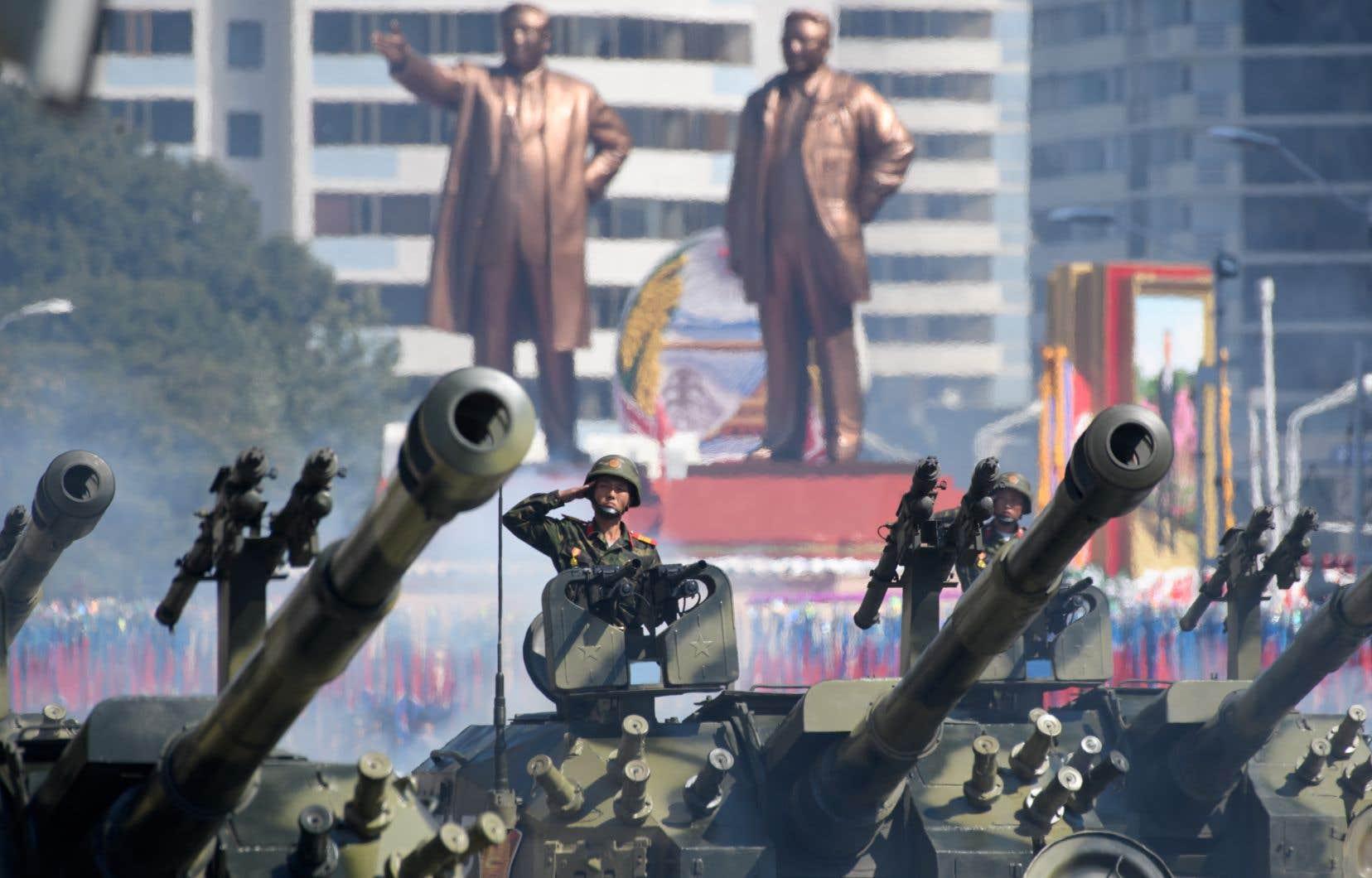 Des soldats de l'Armée populaire coréenne saluent alors qu'ils cunsuident des chars d'assaut lors d'un défilé militaire et d'un rassemblement de masse sur la place Kim Il Sung à Pyongyang, le 9 septembre 2018.