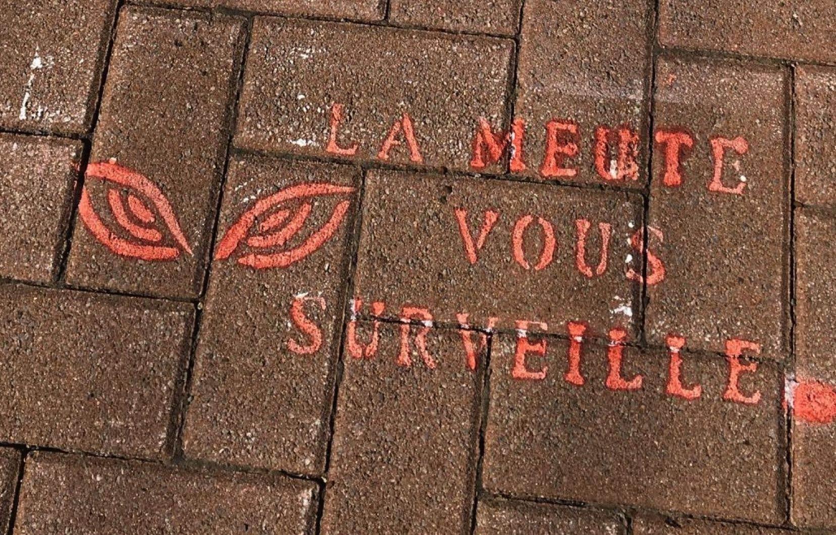 Les graffitis prennent la forme d'une patte de loup blanche avec l'inscription «La Meute vous surveille» et se trouvent sur le trottoir à l'entrée des locaux électoraux.