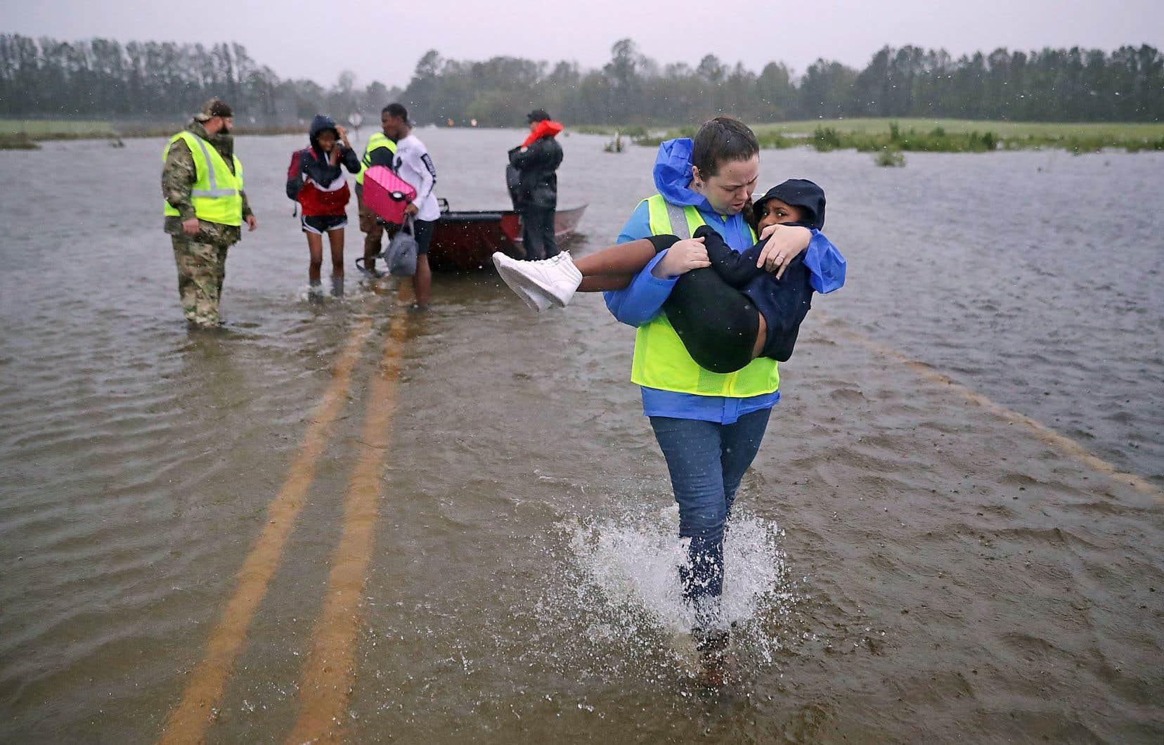 Une bénévole aidait Keiyana Cromartie, 7 ans, et sa famille à quitter leur maison inondée à James City en Caroline du Nord.