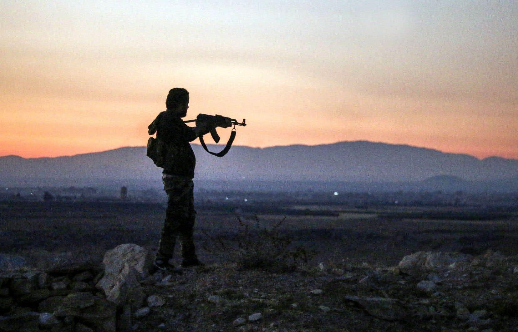 Un rebelle syrien pointe son arme vers la ligne de front près de Damas, en juillet 2018.