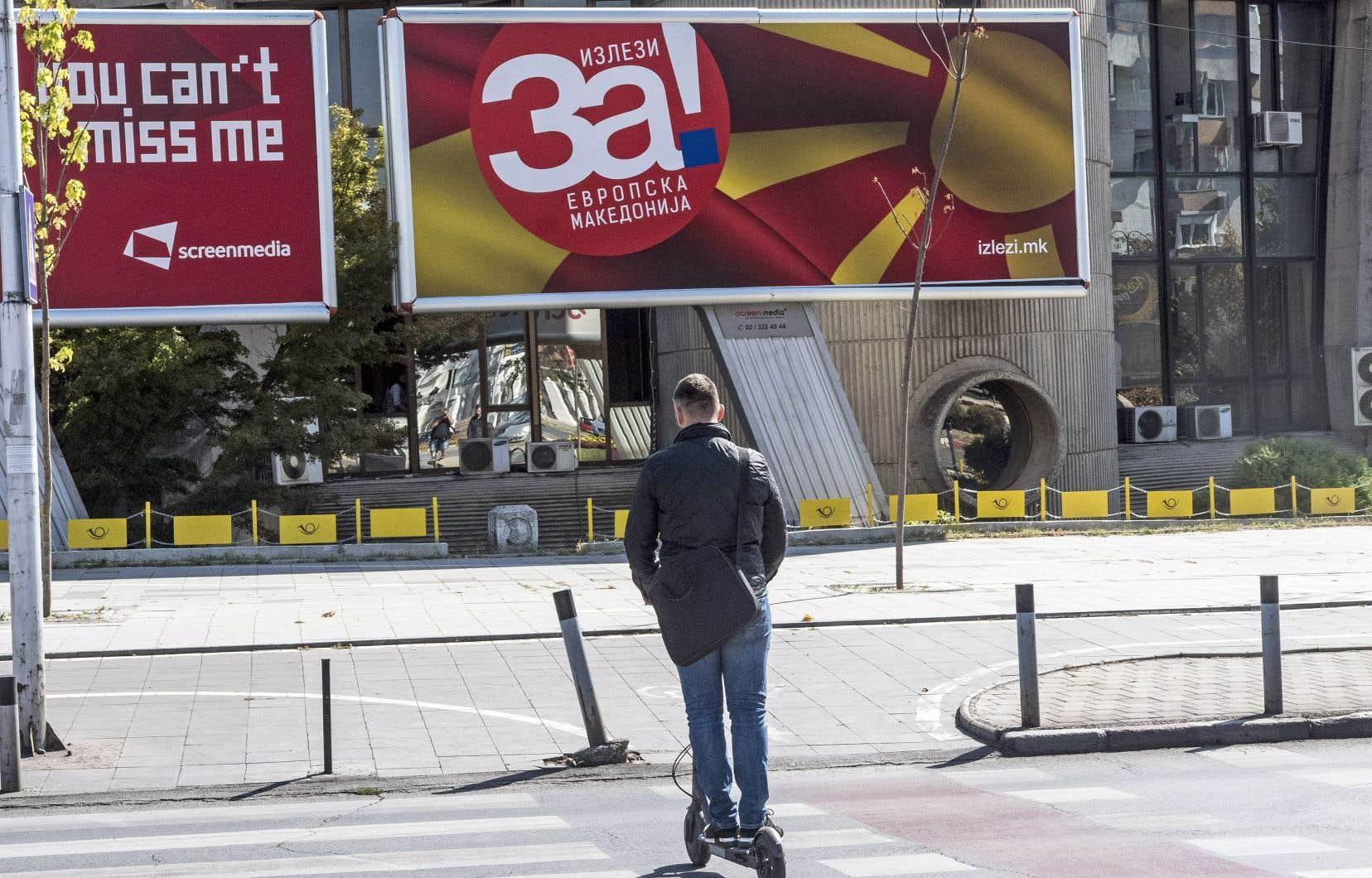 Un passant déambule à Skopje devant une affiche du référendum en Macédoine.