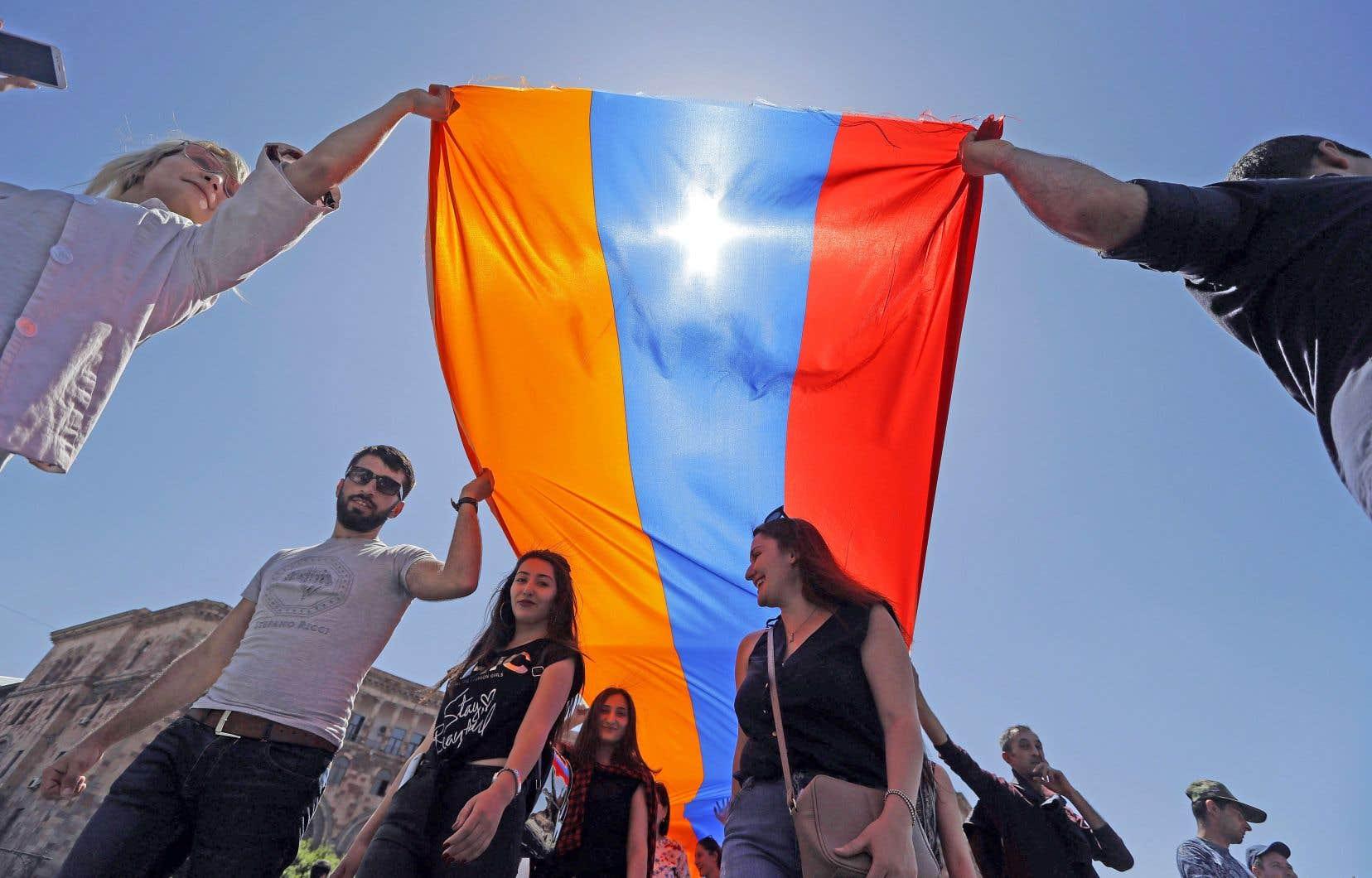 De jeunes Arméniens déploient un drapeau de leur pays.