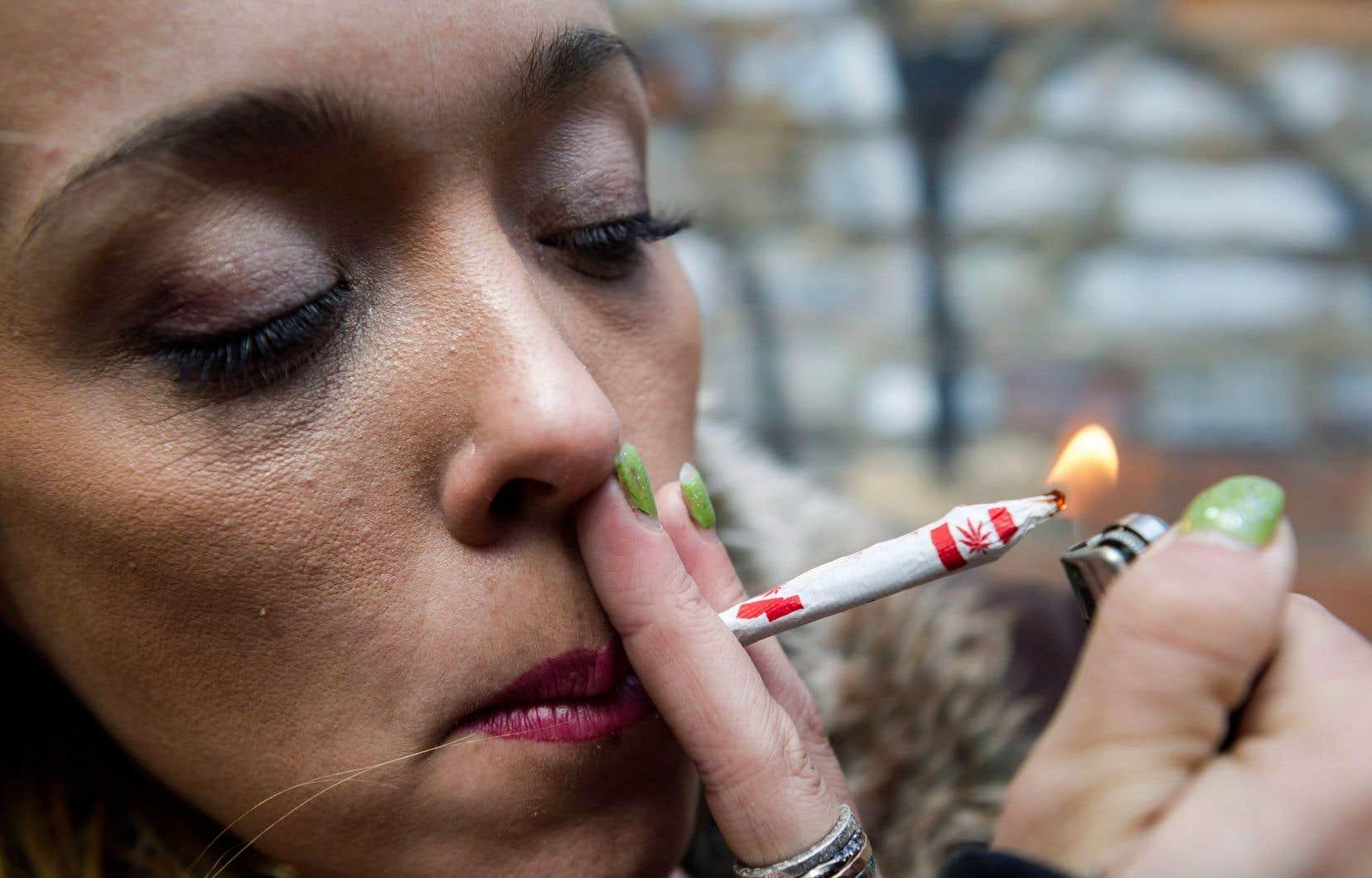 Une femme allume un «joint» orné d'un unifolié modifié.