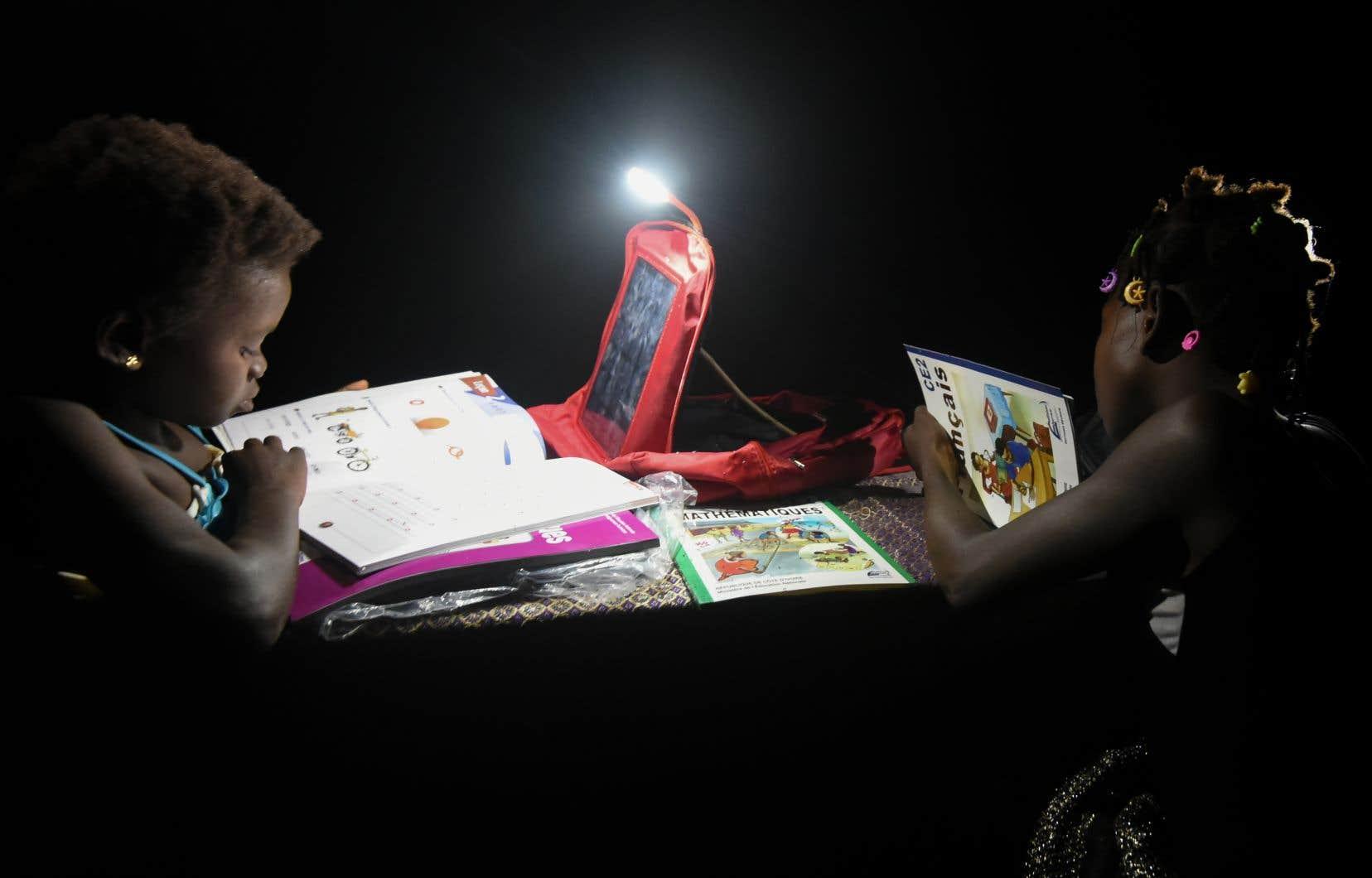 La jeune Lucienne tourne les pages d'un livre àa la lumière de son sac d'école. «Je suis contente», dit-elle. «Avant, c'était plus compliqué.»