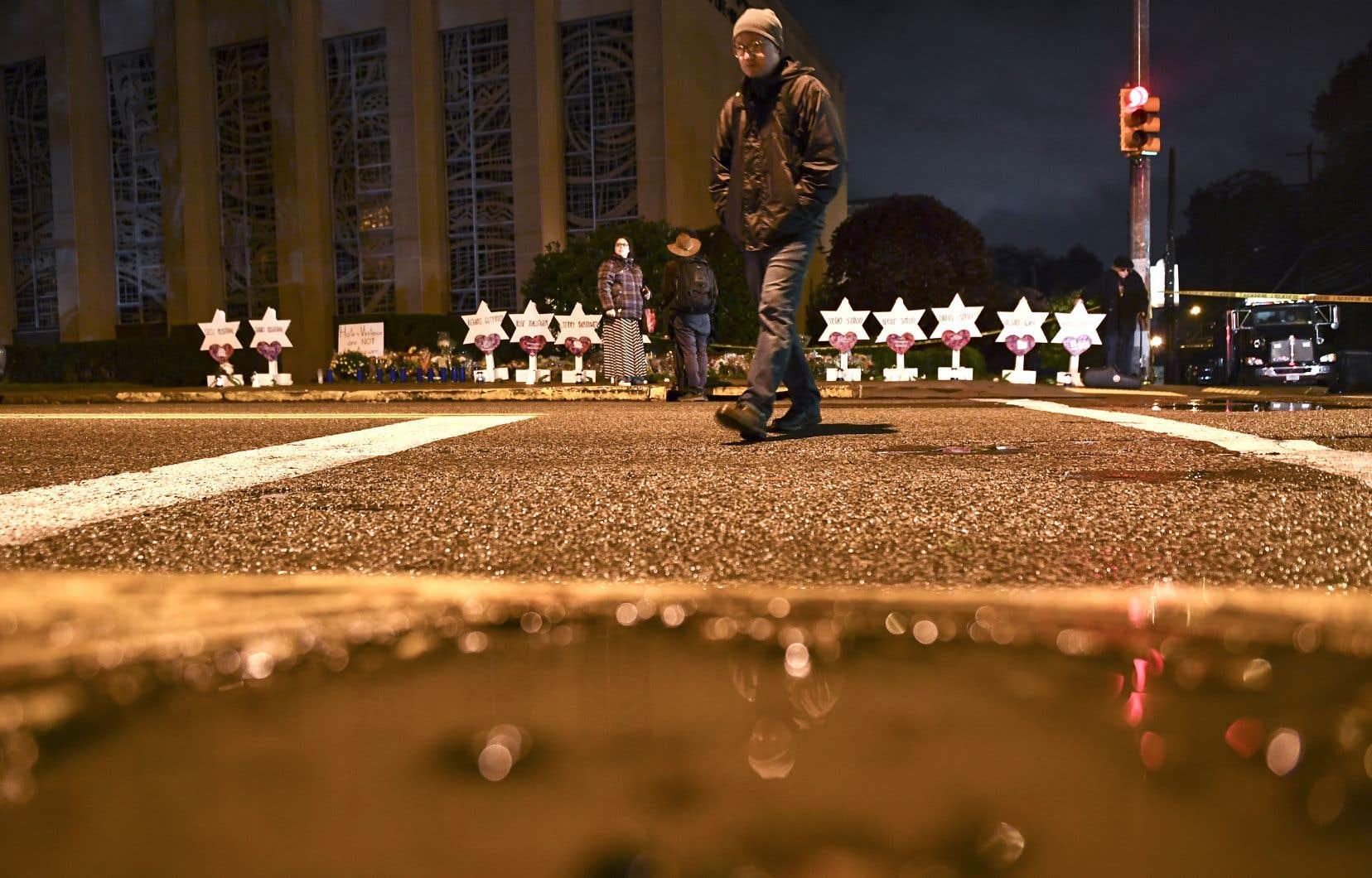 Un homme passe devant un lieu de recueillement spontané dressé en souvenir des 11 victimes de l'attaque de samedi.