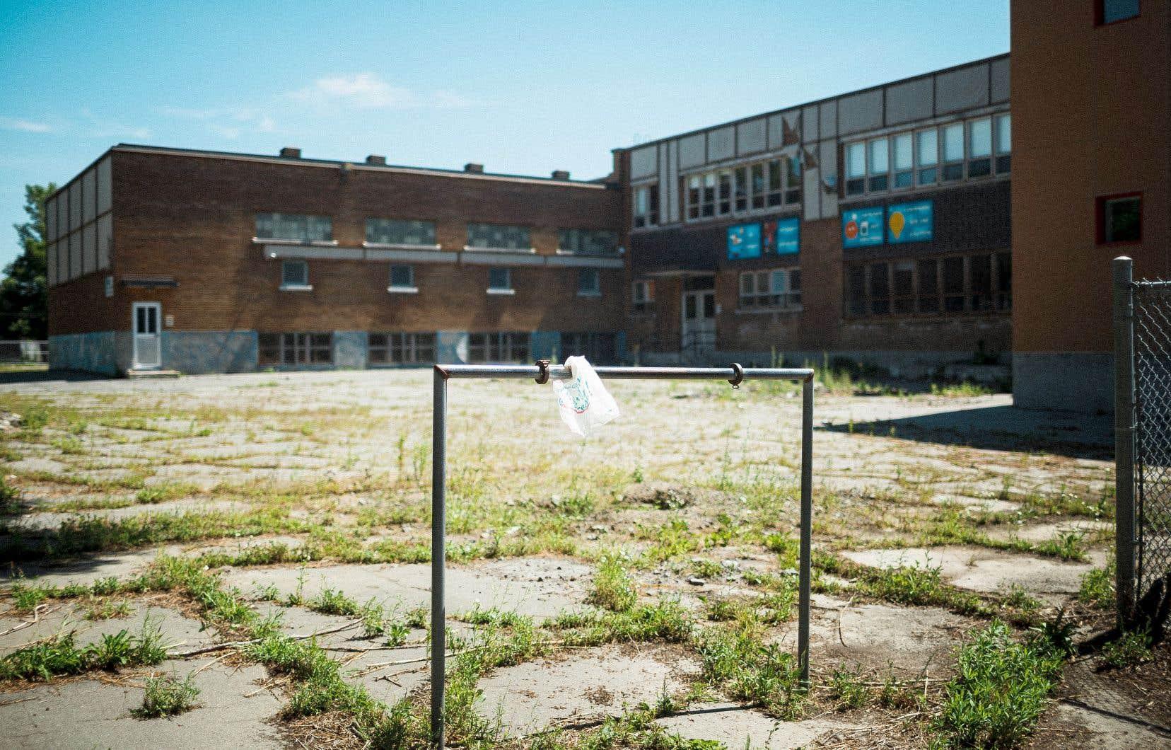 Les mauvaises herbes, qui poussent à travers les craques de l'asphalte dans la cour d'école enclavée par des clôtures tordues, illustrent l'état de décrépitude avancé de l'école Sainte-Lucie, dans le quartier Saint-Michel.