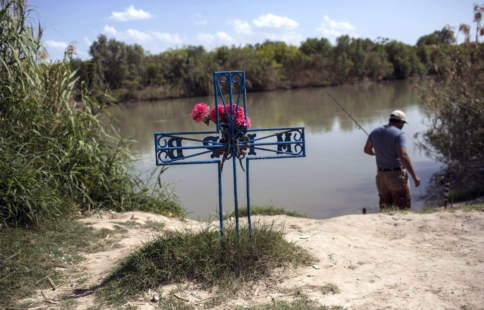 Un homme pêche dans le Rio Grande à Laredo au Texas, près d'une croix plantée en mémoire d'un immigrant qui s'est noyé en tentant d'entrer aux États-Unis à la nage.