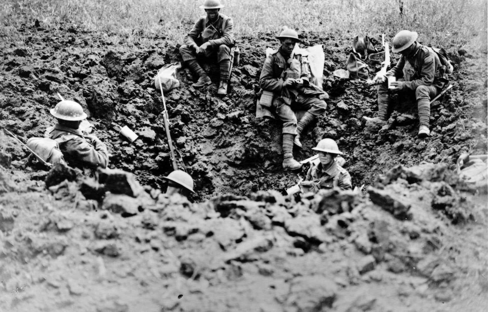 Des militaires canadiens se reposent dans des trous d'obus en marge de la bataille d'Amiens, en août 1918.