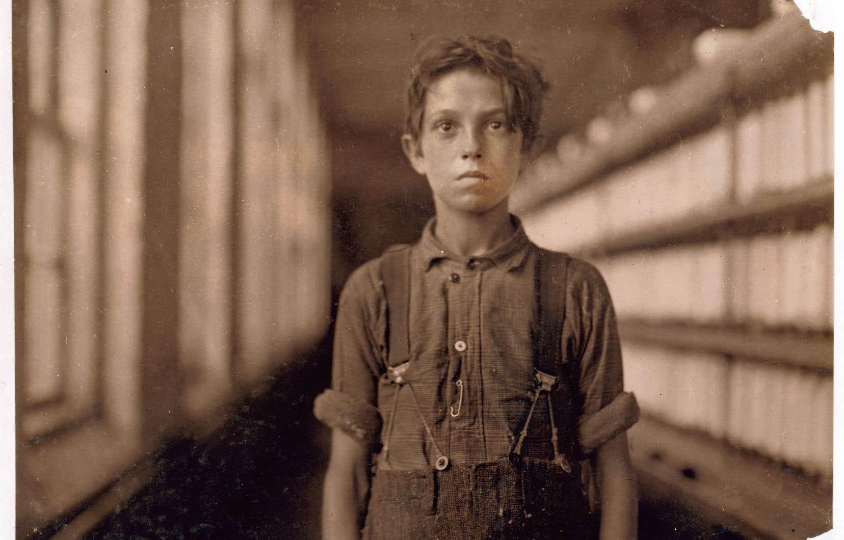 Parmi les milliers d'immigrants canadiens-français qui peinent dans les usines de la Nouvelle-Angleterre, on trouve des enfants. Le sociologue et photographe Lewis Hine documente leurs conditions de travail. Il note à l'oreille leurs noms. Ici «Jo Bodeon», Joseph Beaudoin, photographié à la Chace Cotton Mill de Burlington, au Vermont, en 1909.