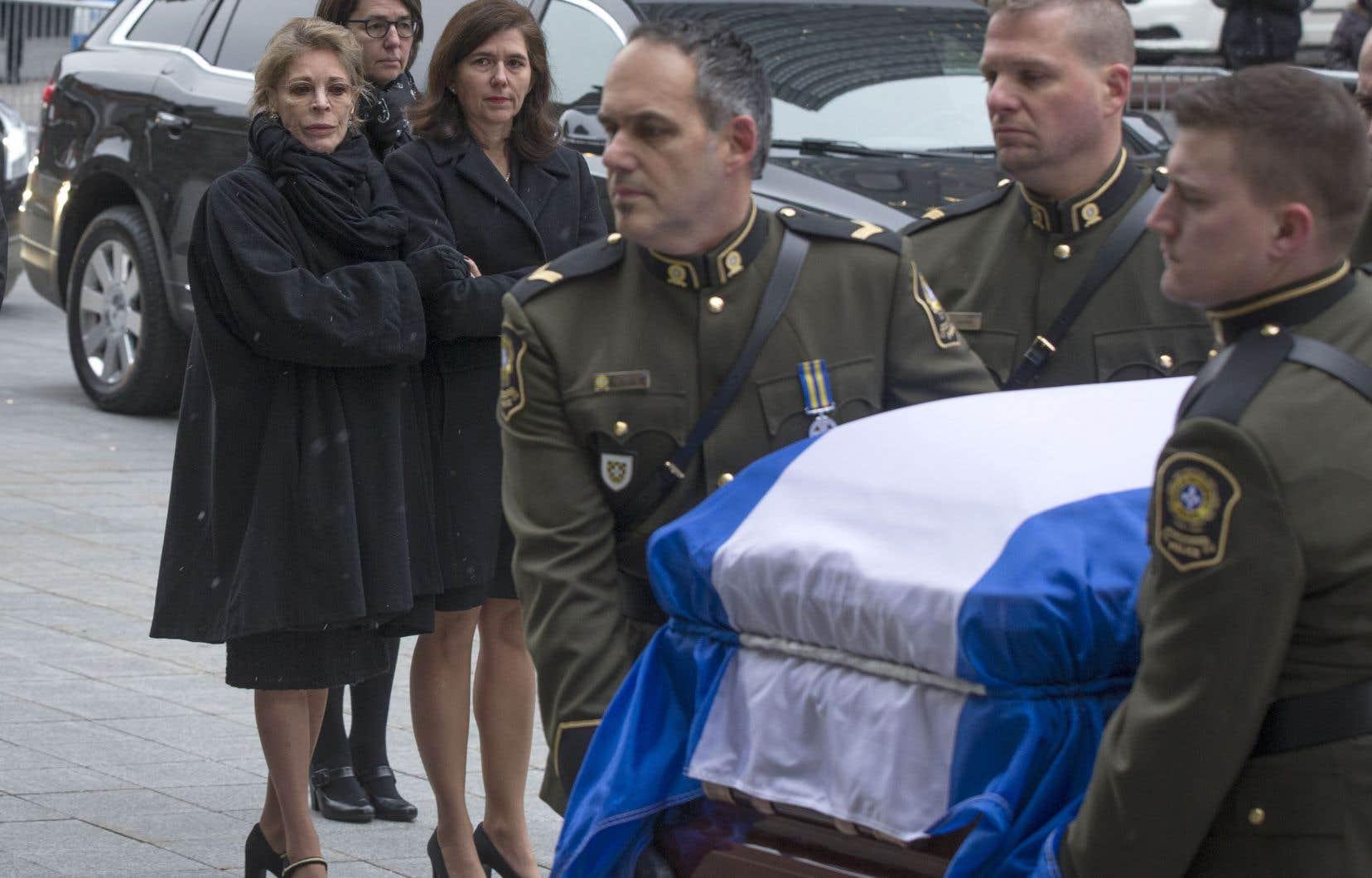 L'épouse et la fille de Bernard Landry, Chantal Renaud et Pascale Landry, ont regardé avec émotion le cercueil de l'ancien premier ministre du Québec être porté par des policiers de la Sûreté du Québec sur le parvis de la basilique Notre-Dame, à Montréal.