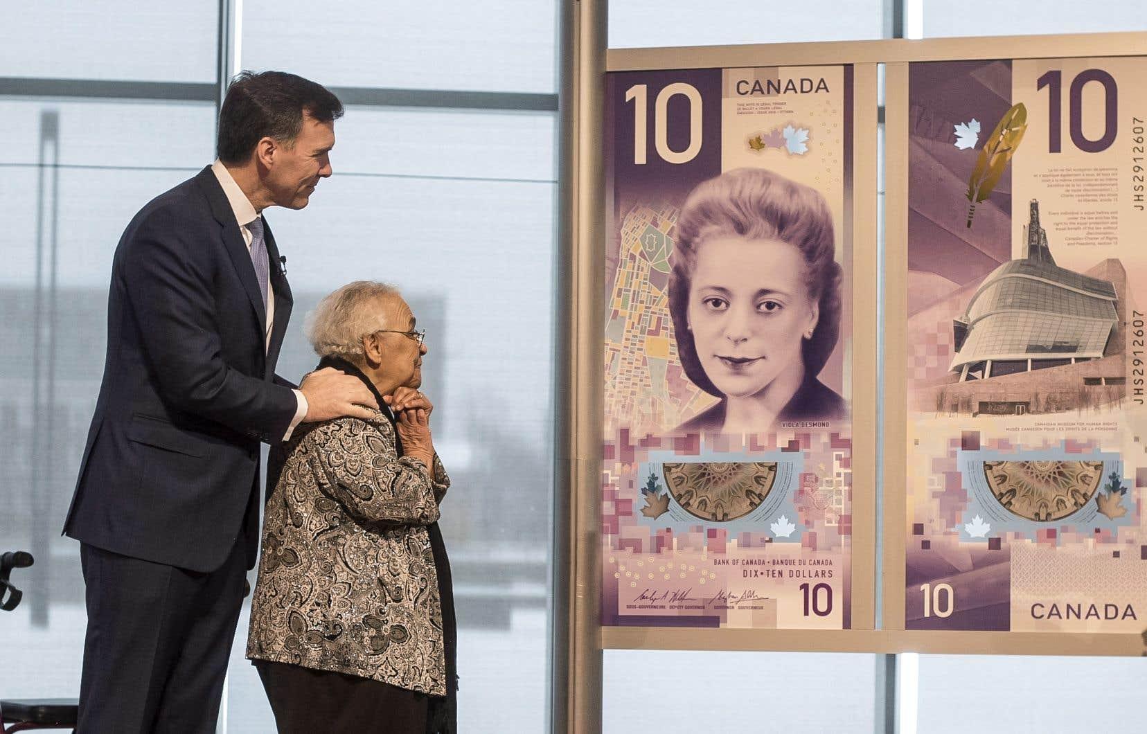 Wanda Robson, la soeur de Viola Desmond, admire le billet de 10$ conçu à son effigie en compagnie du ministre canadien des Finances, Bill Morneau.