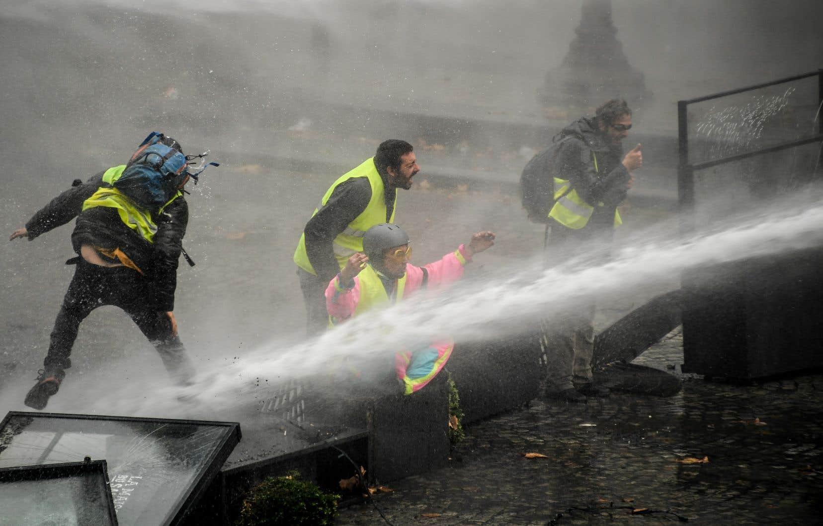 Des «gilets jaunes» sont aspergés par un canon à eaulors d'une manifestation contre la hausse du prix du pétrole et du coût de la vie,près de la place de la Concorde, à Paris.