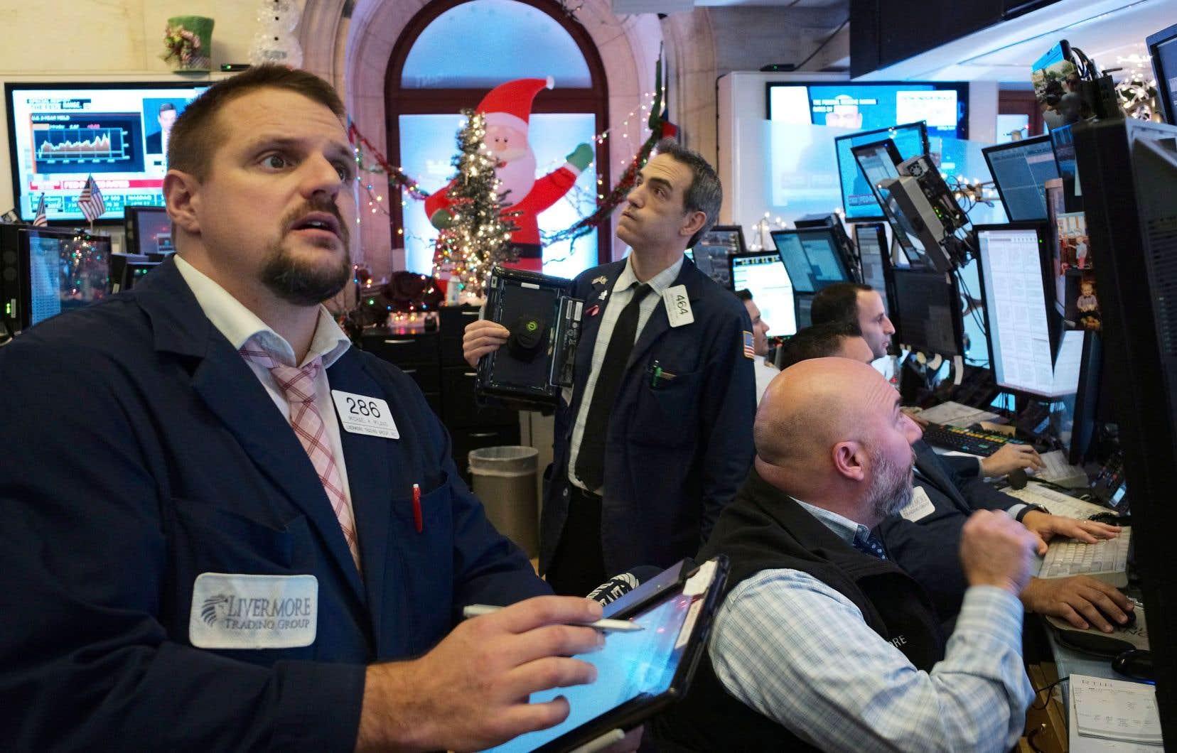 Des courtiers réagissant à la hausse du taux de la Fed, mercredi