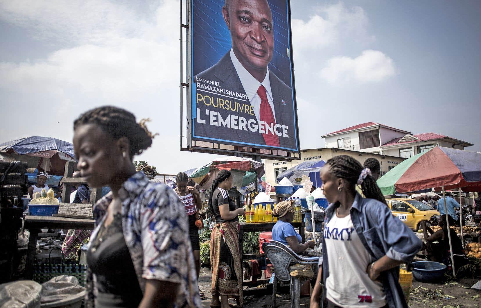 Des passants circulant devant une affiche électorale du candidat à la présidentielle reportée Emmanuel Ramazani Shadary, dauphin de Joseph Kabila, dans la capitale de Kinshasa, le 18décembre dernier