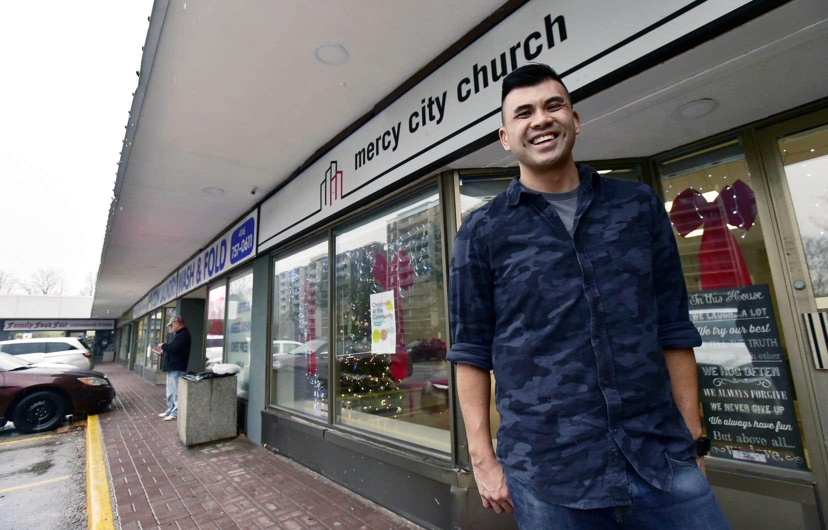 Le pasteur Chris Yu pose devant l'église Mercy City, à Toronto, nichée entre une buanderie et une ancienne pharmacie.