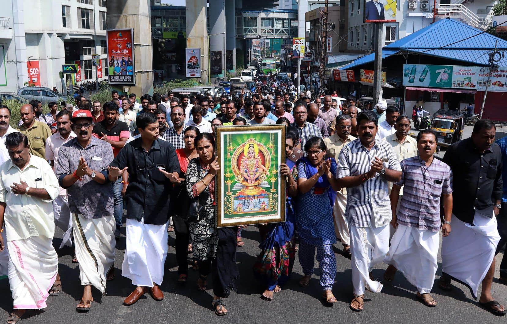 Des manifestants en Inde portent une photo de la divinité hindoue Ayyappa lors d'une manifestation qui a suivi l'entrée de deux femmes au temple Sabarimala, à Kochi, dans le sud de l'État de Kerala, le 2 janvier 2019.