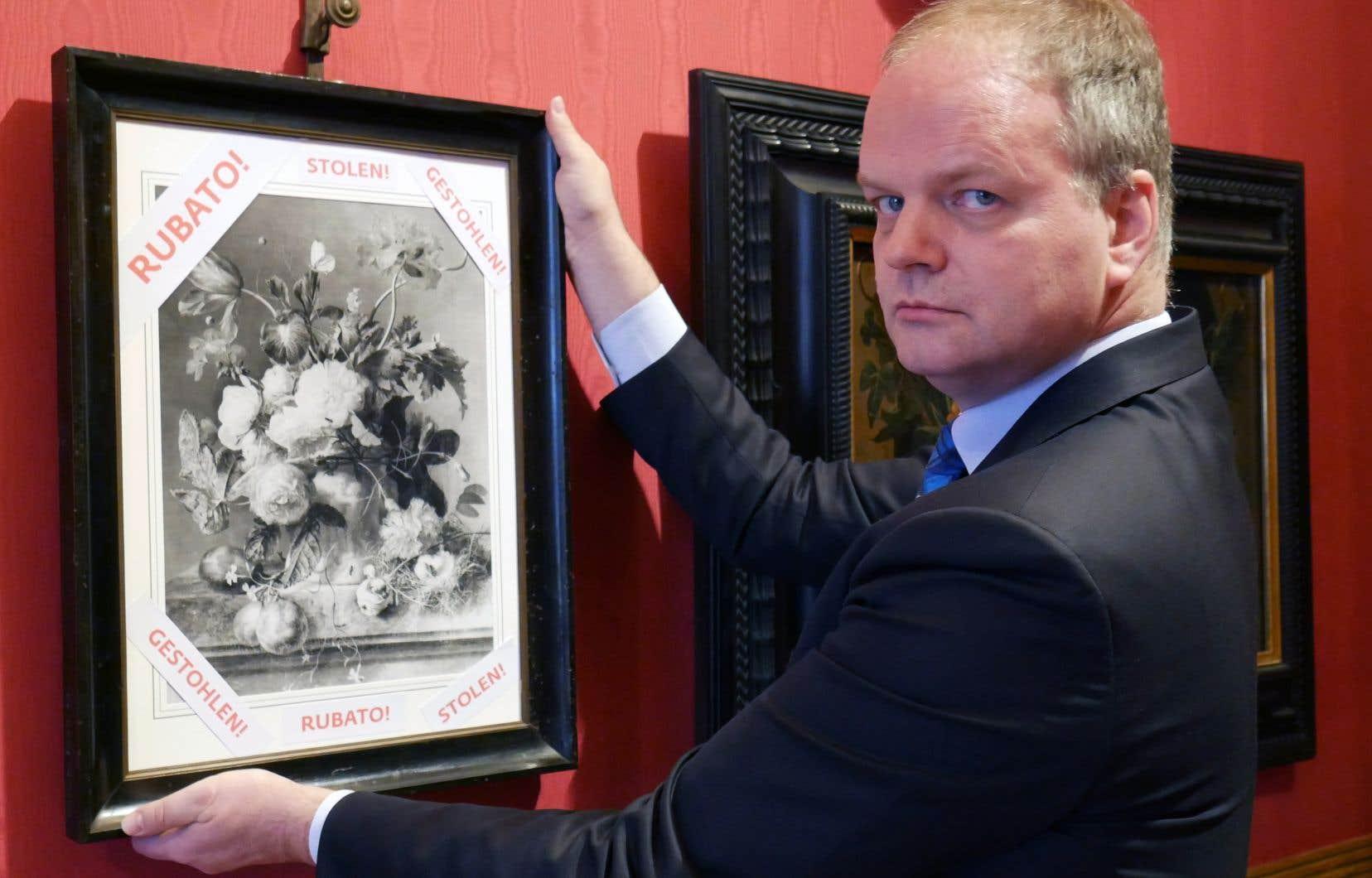 Le directeur de la galerie des Offices de Florence,Eike Schmidt, tenant une photo en noir et blanc dela nature morte «Vase de fleurs», de l'artiste hollandais Jan van Huysum (1682-1749).