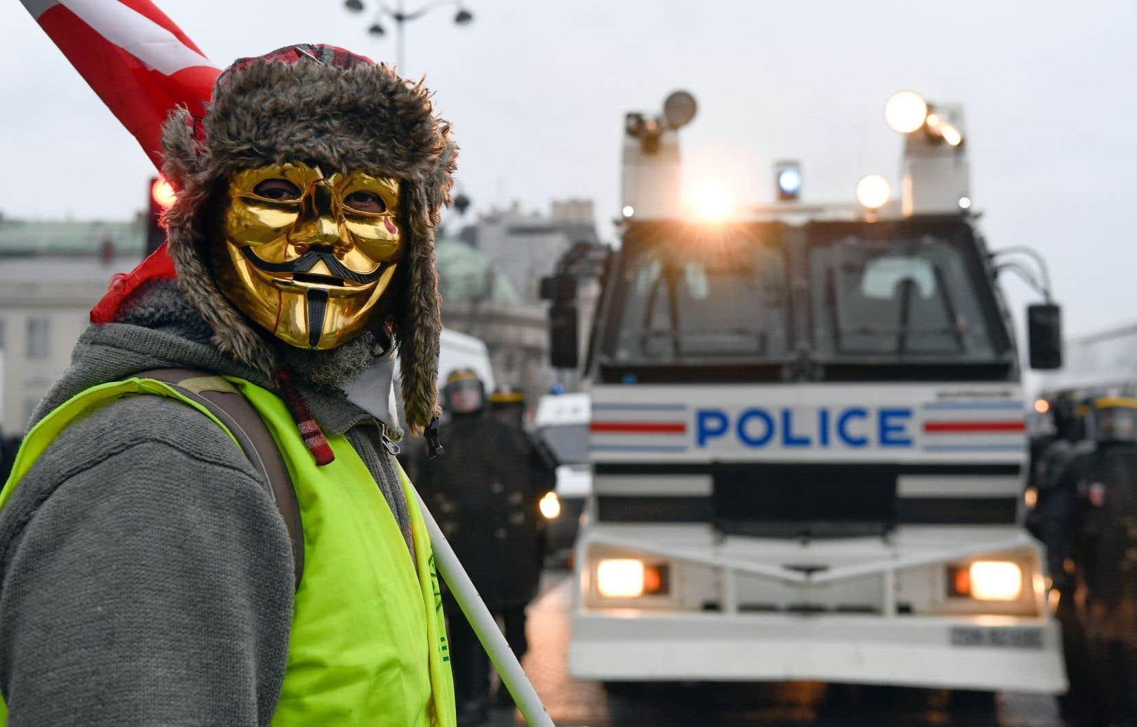 Un membre des gilets jaunes, arborant un masque de Guy Fawkes doré, a été photographié devant un véhicule policier lors des manifestations de samedi dernier à Paris.