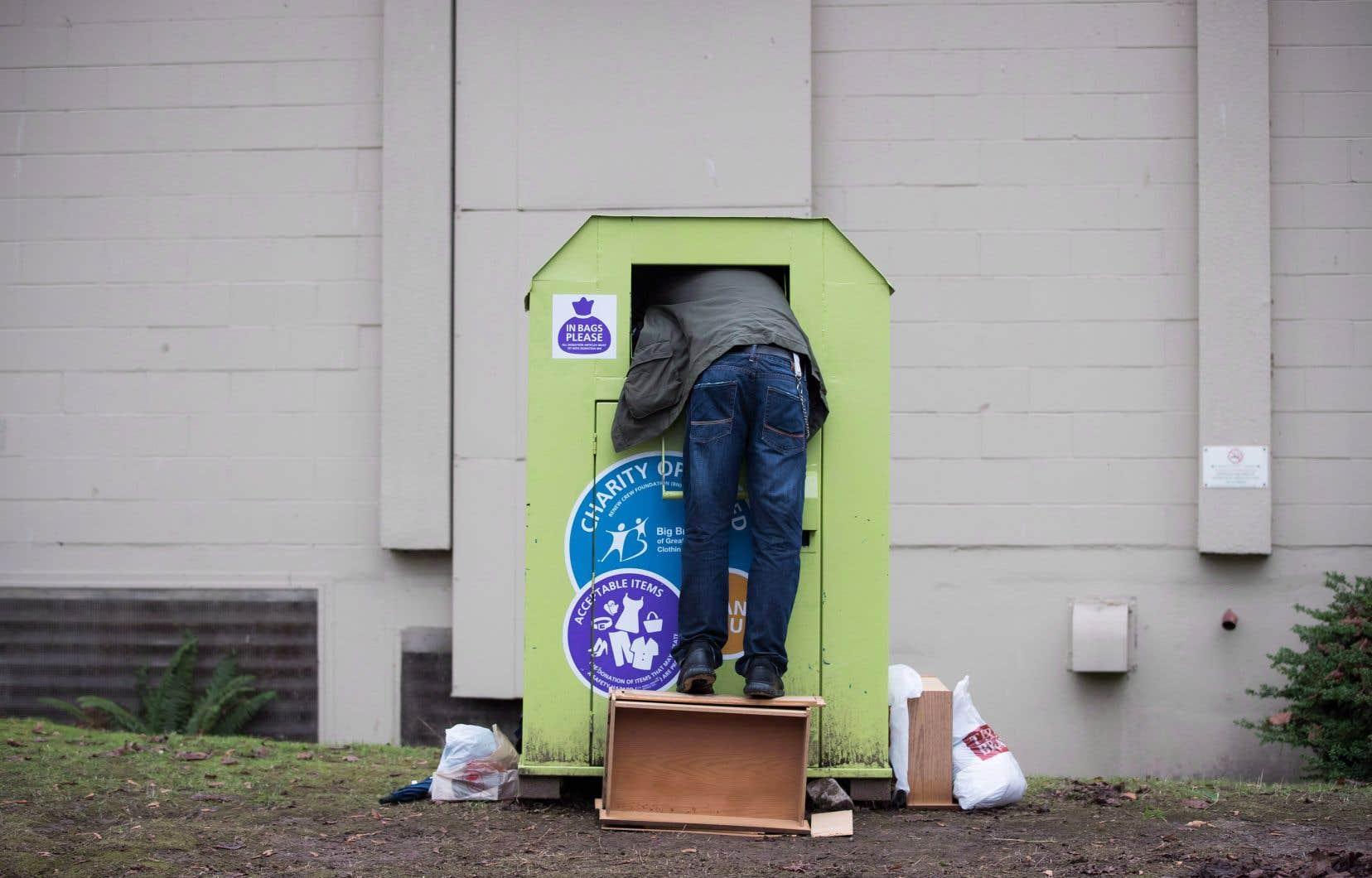 Un homme tente de récupérer des objets dans un bac de dons de vêtements à Vancouver.