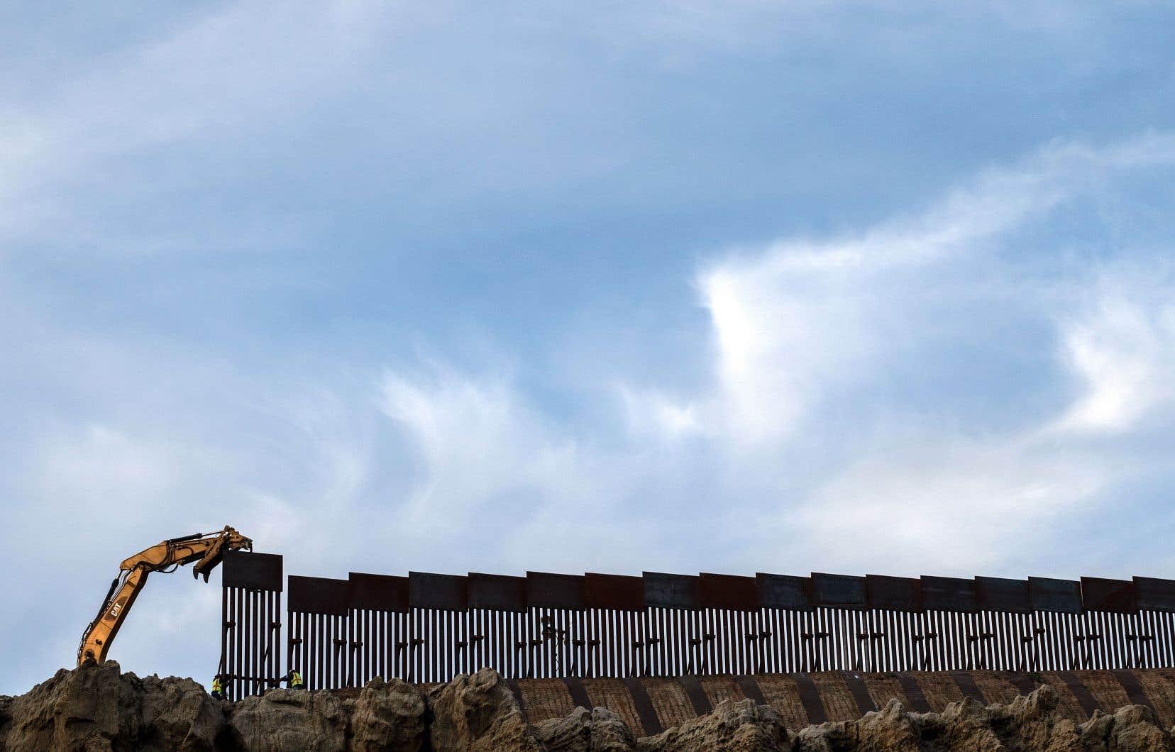 Des employés remplacent une vieille barrière à la frontière américano-mexicaine à Tijuana.