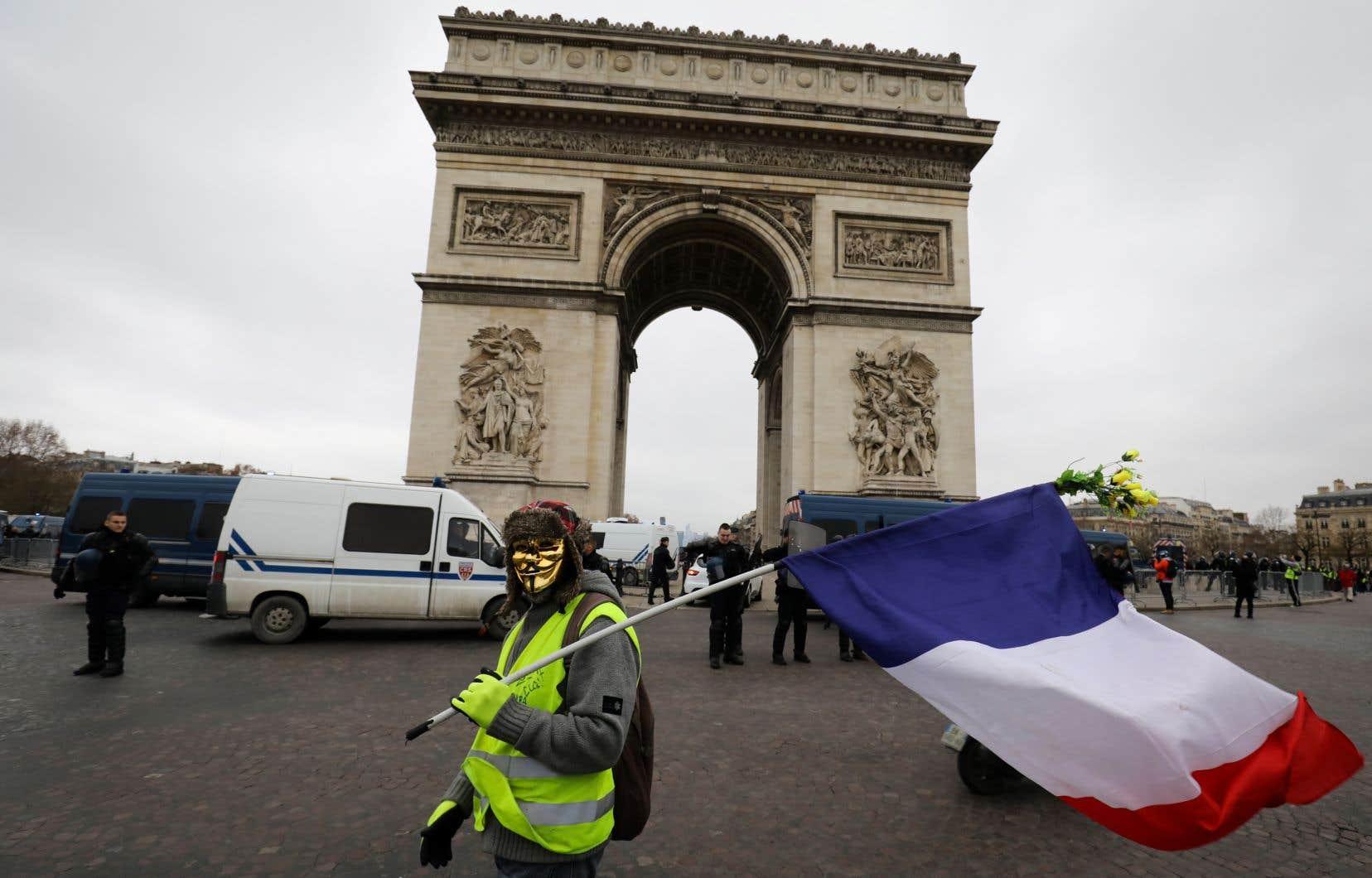 Un manifestant portant un masque de Guy Fawkes et un gilet jaune brandit un drapeau français devant l'Arc de Triomphe lors d'une manifestation à Paris.