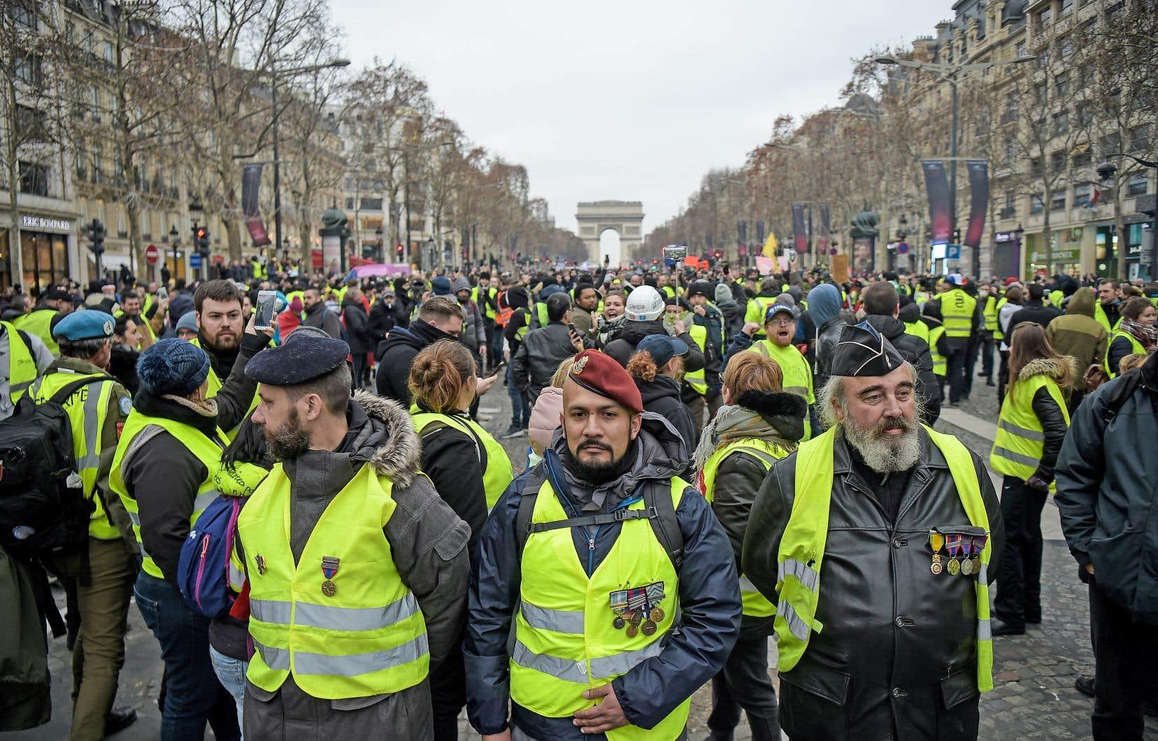 D'anciens soldats français ont épinglé leurs médailles militaires sur leurs gilets jaunes avant de se joindre aux manifestations sur les Champs-Élysées, samedi.