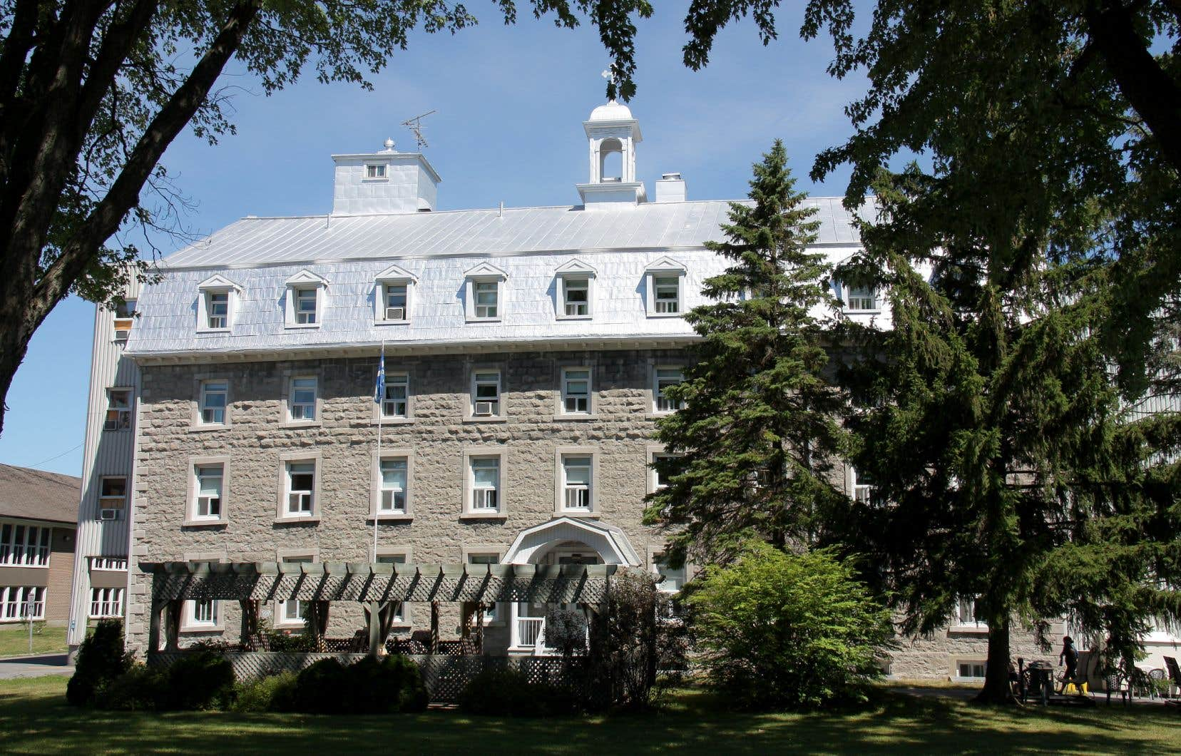 Le bâtiment original est en pierres grises. Il fait face au presbytère, lui aussi en pierres grises.
