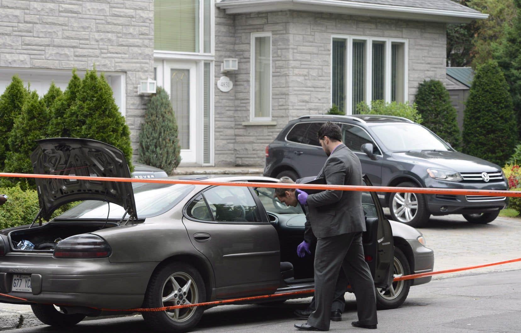 Des policiers examinent un véhicule stationné devant la maison de l'entrepreneur Tony Magi, en juillet 2013.